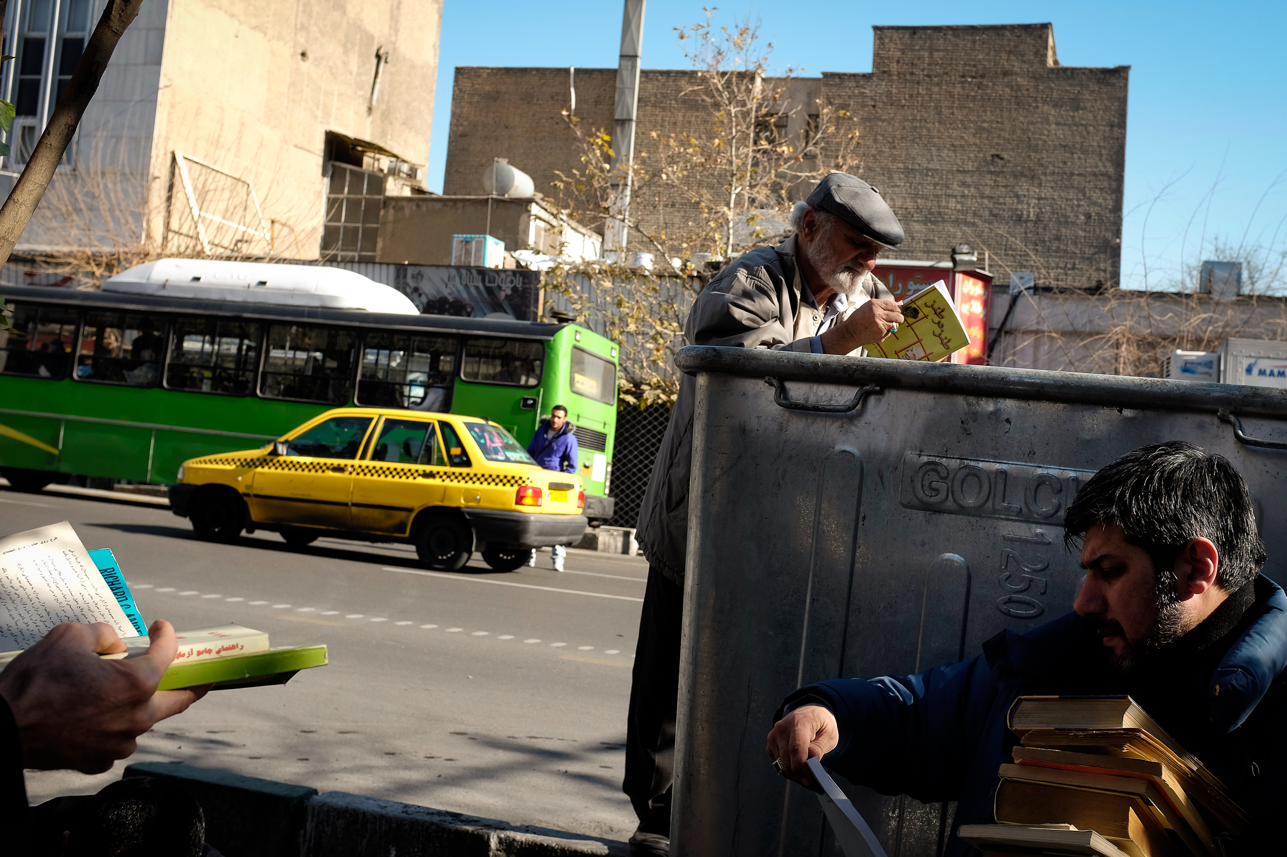 Men skim through a pile of discarded books on the side of a road in central Tehran.