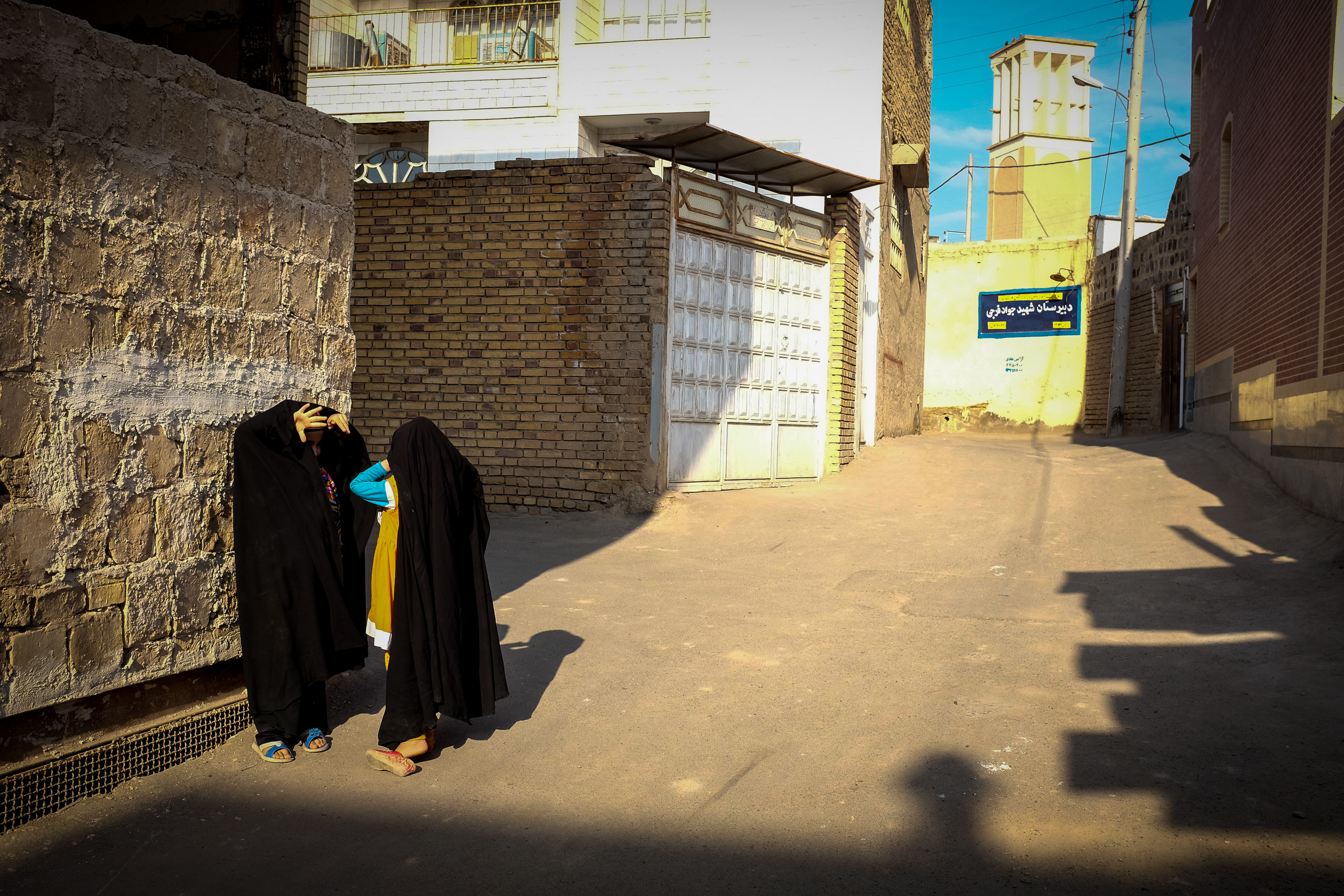 Two young girls play hide and seek in the back streets of Kashan. It is around the age of puberty that girls start to wear the hijab properly, but many start younger to become accustomed to it.