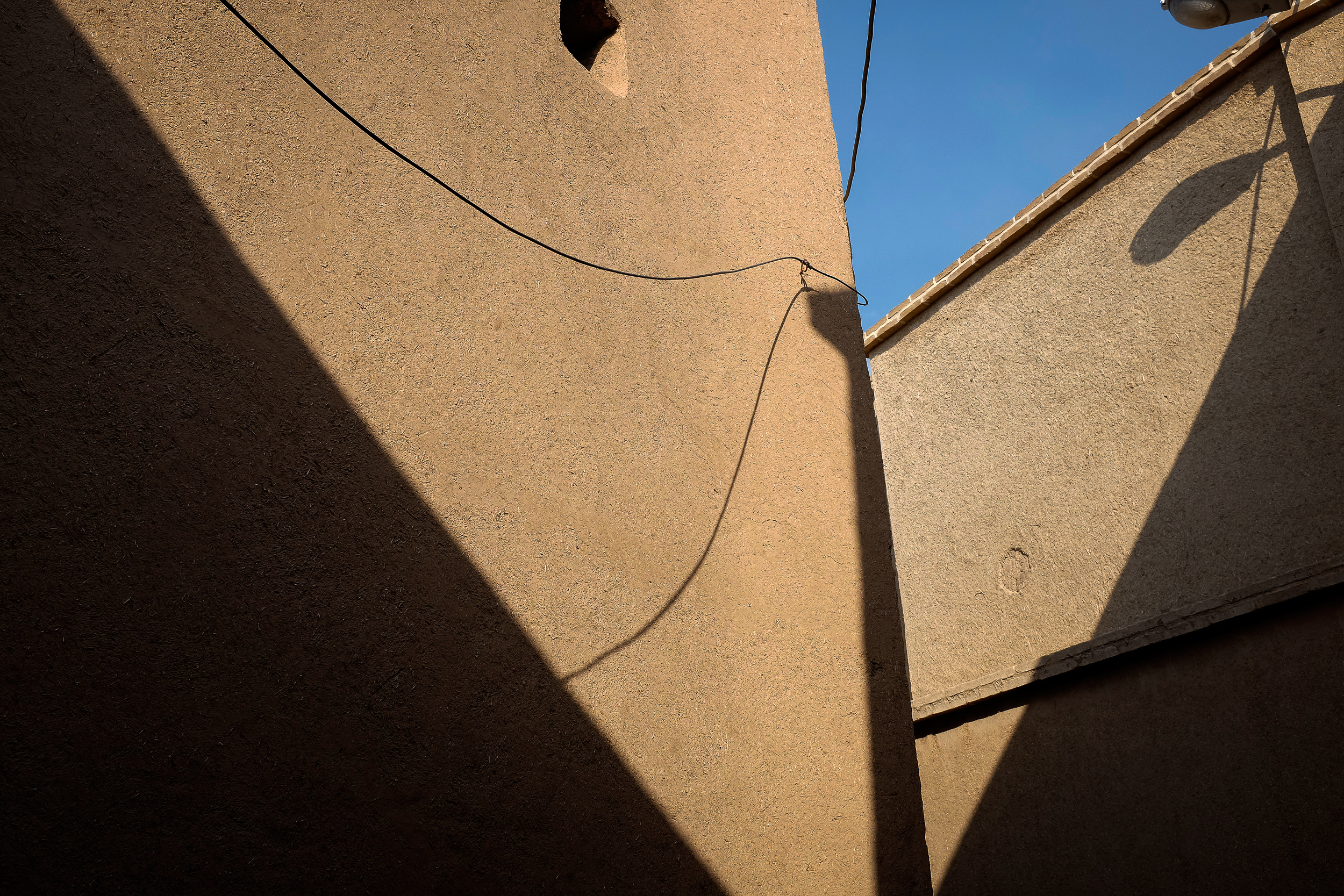 Shadows fall on the ancient dry clay walls of Kashan.