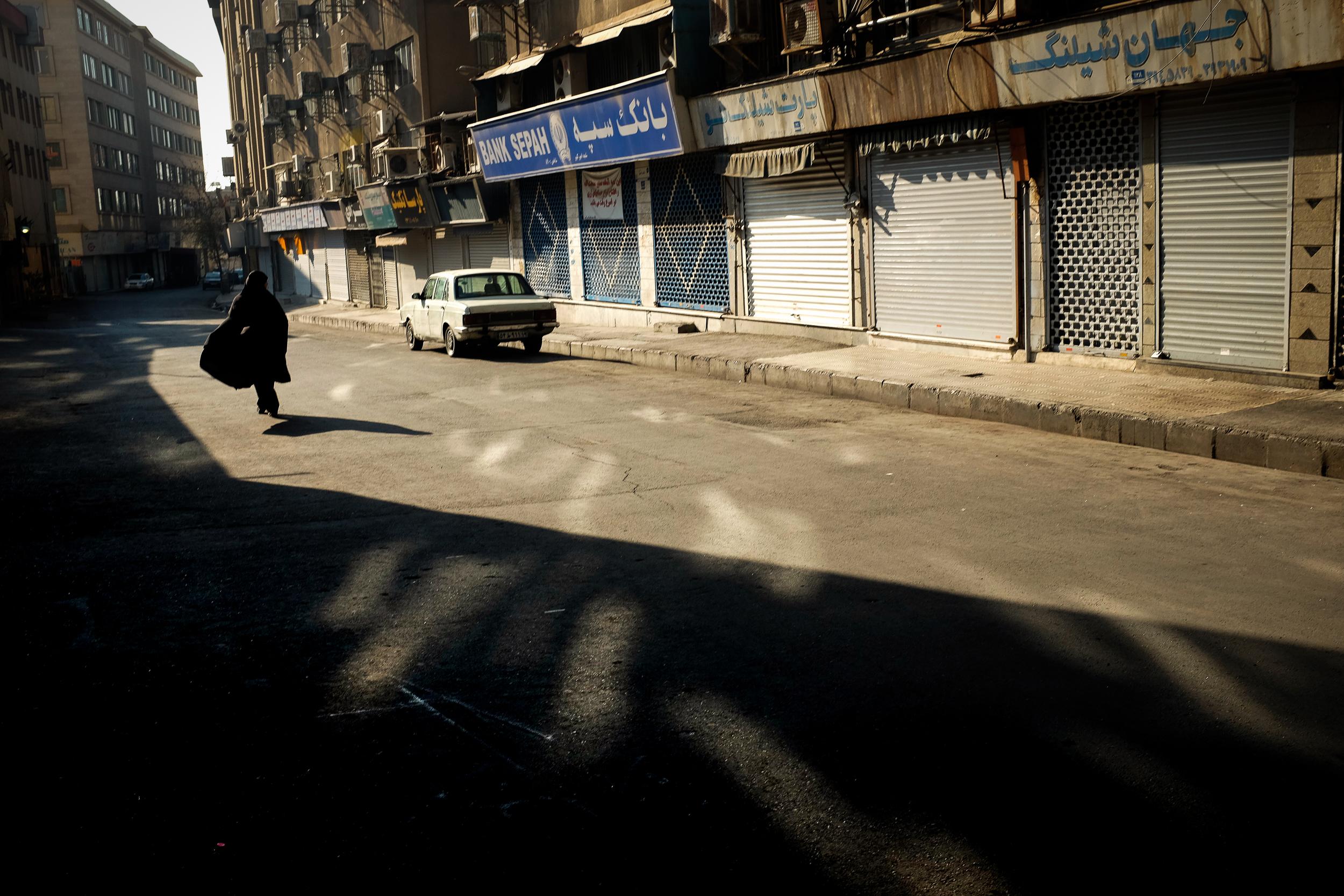 A woman walks down an empty street in Tehran.