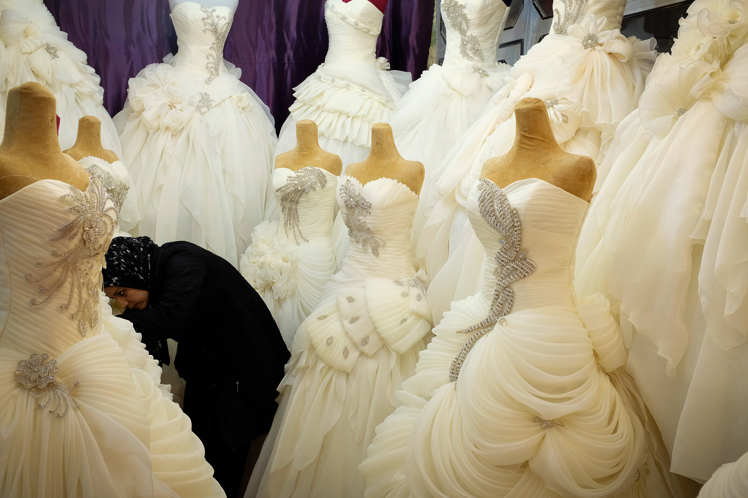 A shopkeeper straightens some wedding dresses in Kashan. Despite women being very restricted in how they can dress in public in a traditional city like Kashan, the full array of fashion – from iconic western brands (usually fake) to your more traditional Persian garments – can be found most large bazaars.