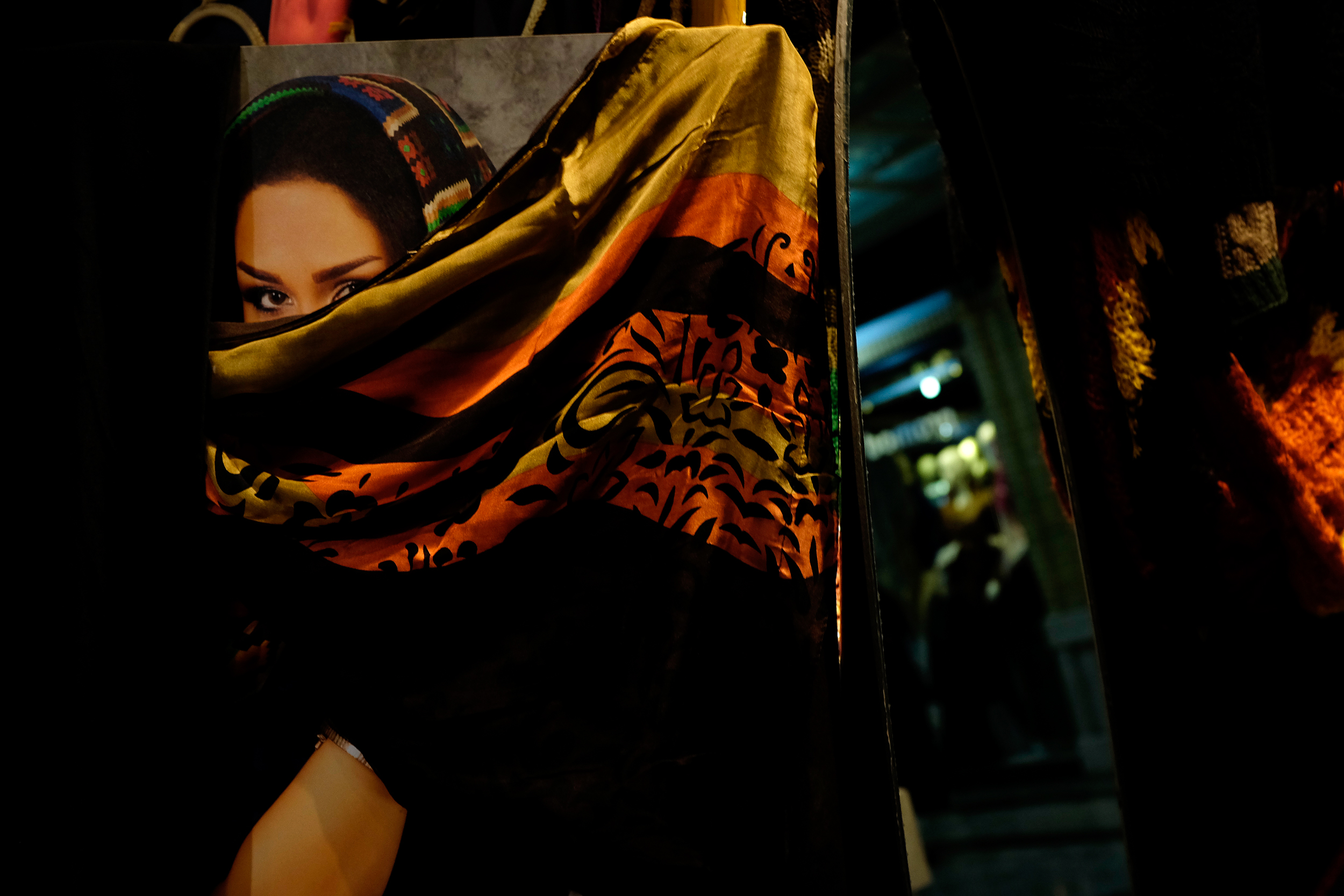 A print of a woman is covered by a headscarf in a bazaar in Central Tehran.