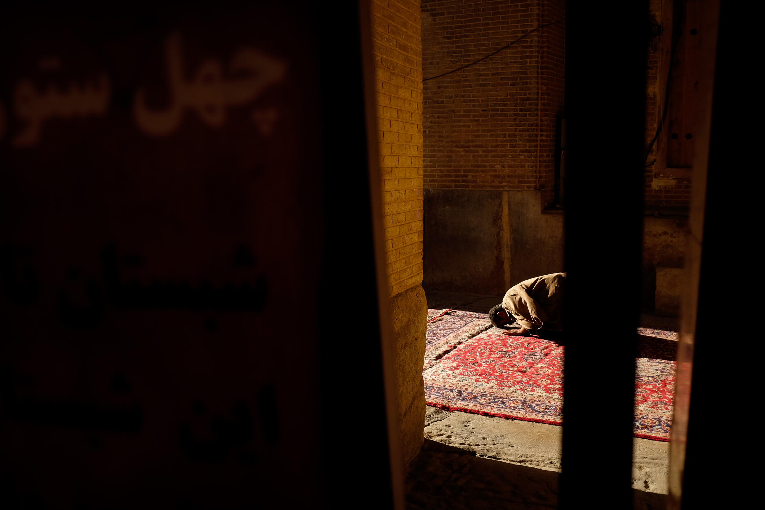 A man prays towards the setting sun in a mosque in Shiraz.