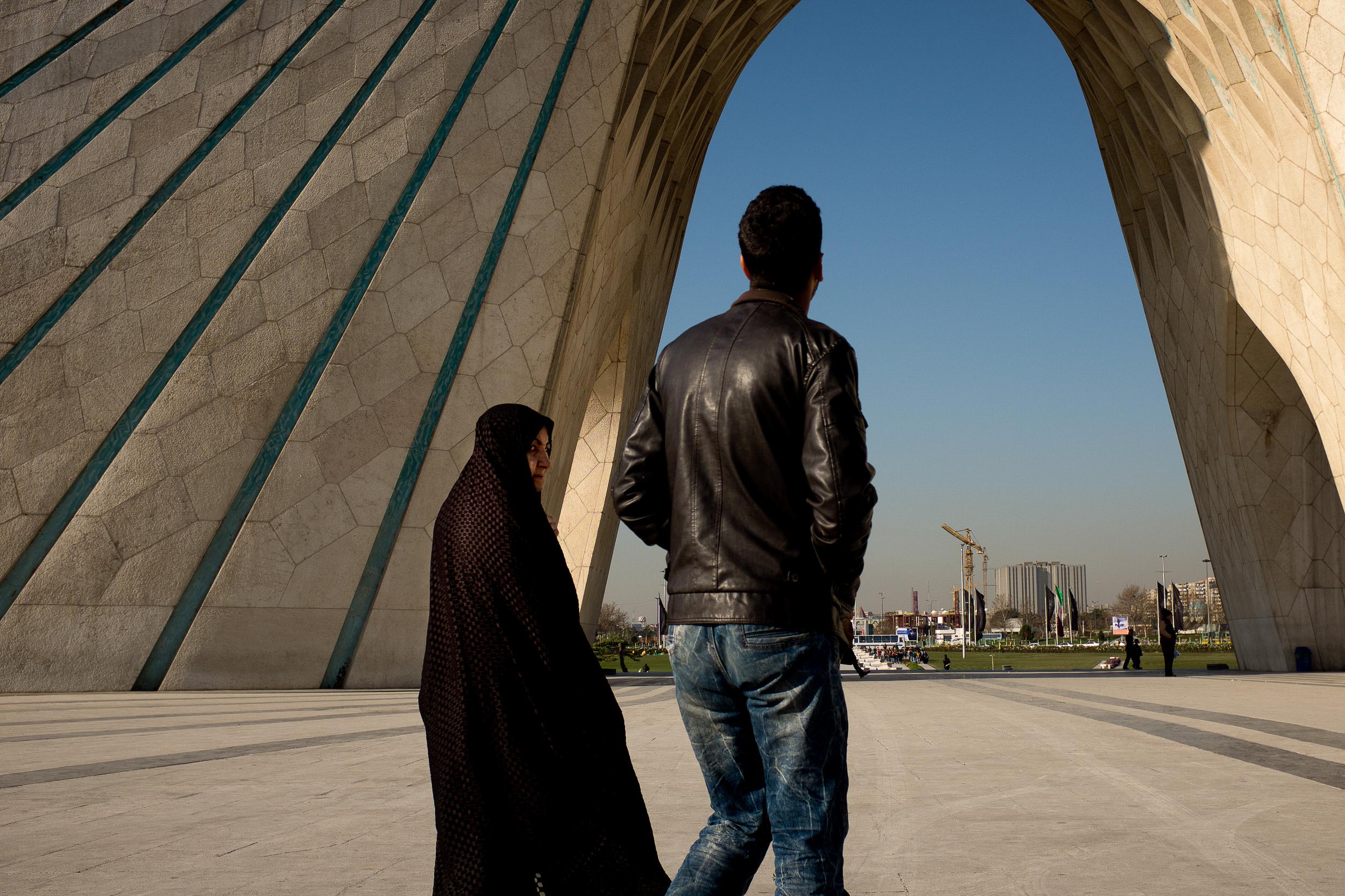 A woman casts her eye sideways as she walks underneath the Azadi Tower in Tehran.