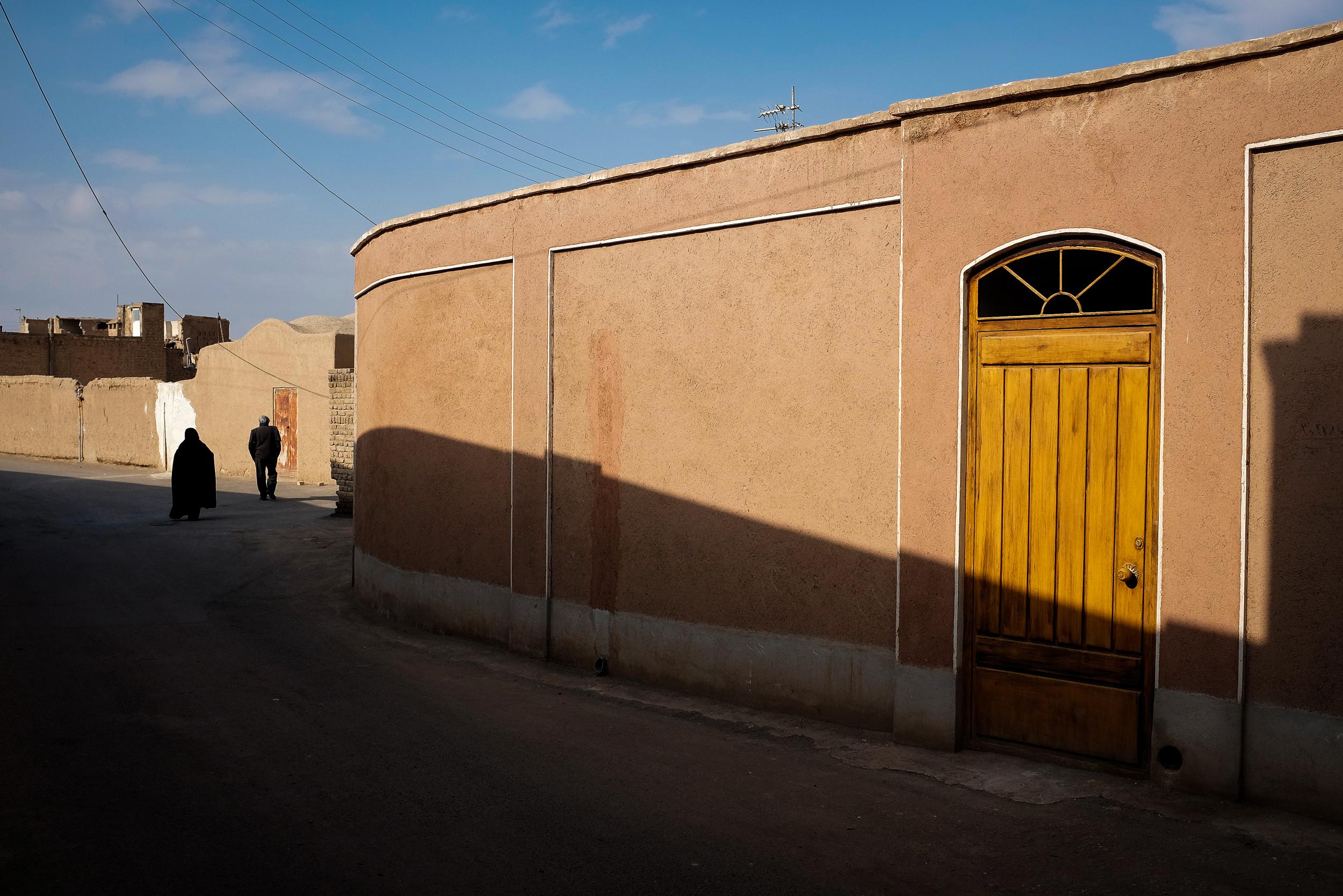 A wife walks behind her husband in Kashan.