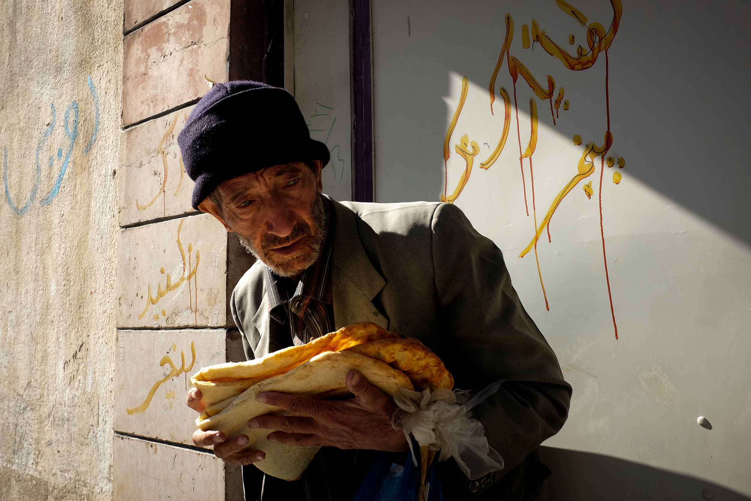 An elderly man clings to his bread in the back alleys of Shiraz.