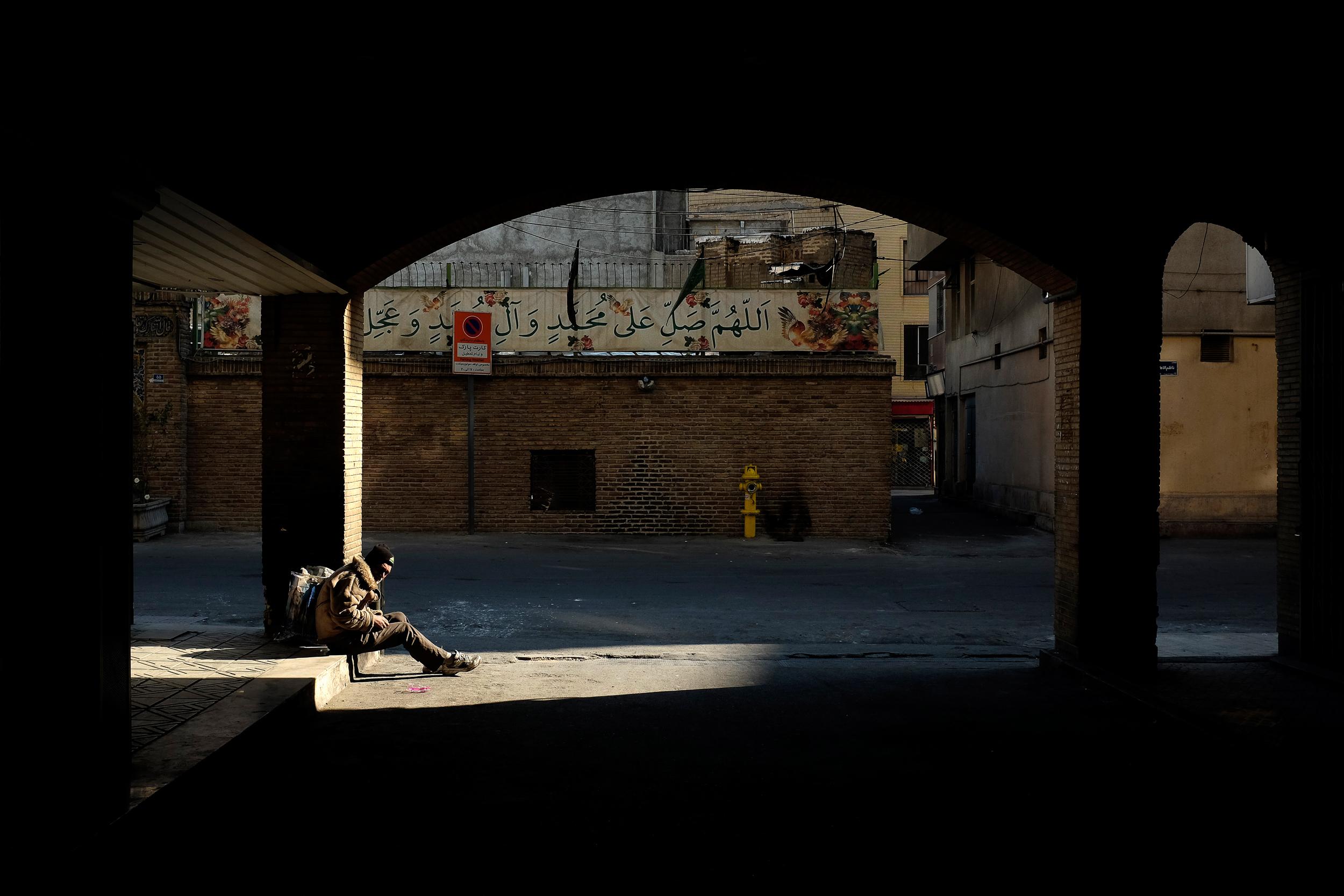 An addict is illuminated by the sun under a bridge in Central Tehran.