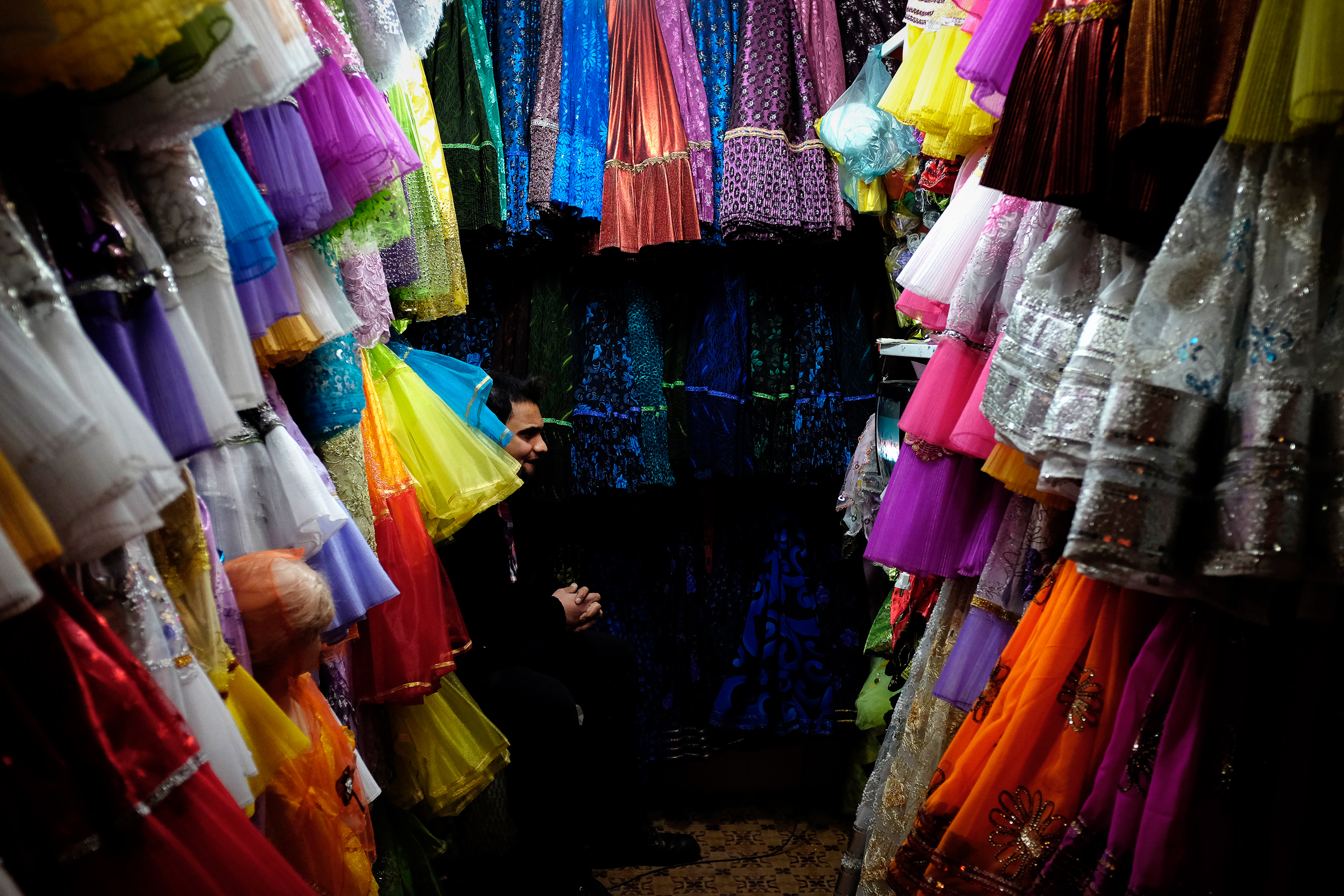 A man watches a local football game in his fabric store in Esfahan.
