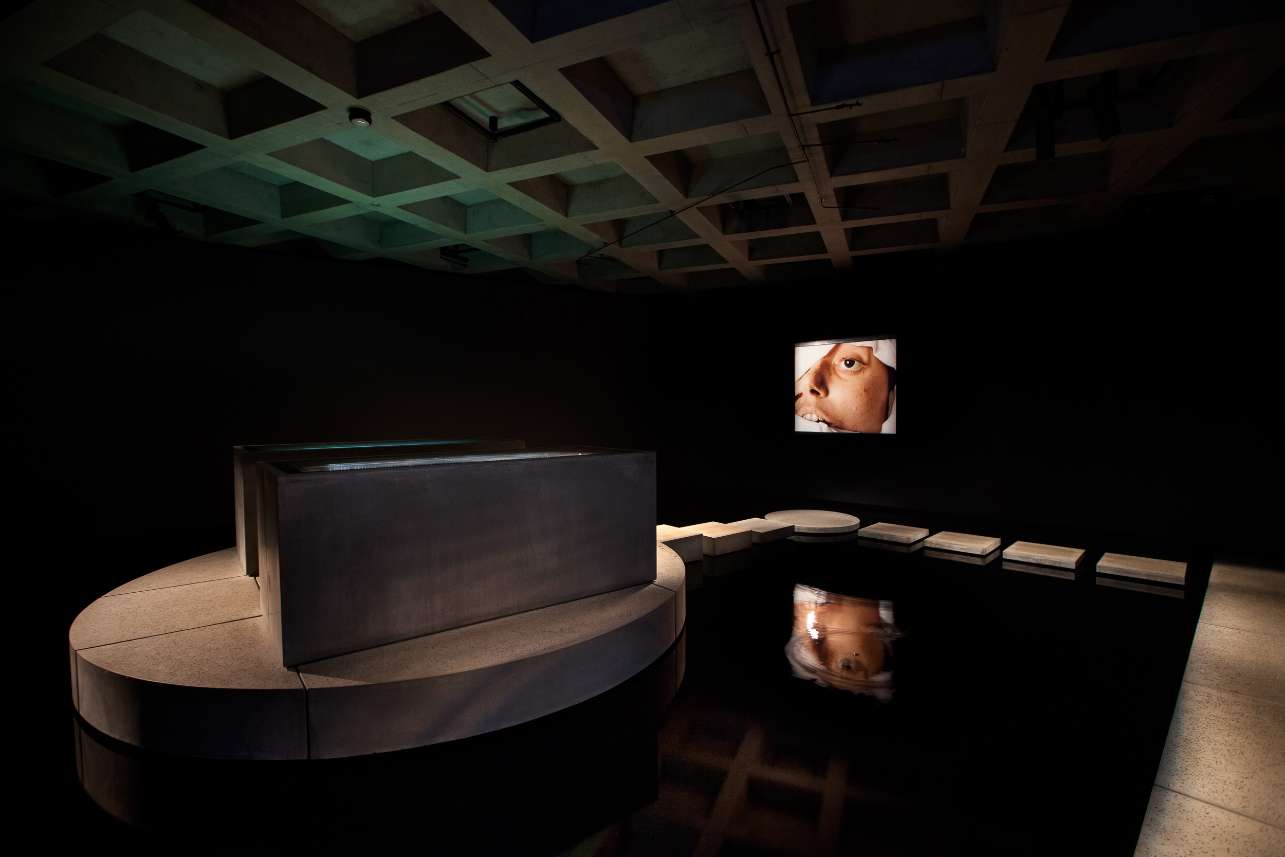 Left: Mummy and Coffin of Pausiris 100 BCE to 100 CE  Human remains encased in stucco plaster with glass eyes, incised and painted decoration  Right wall: The Morgue (Blood Transfusion Resulting In Aids), 1992  Andres Serrano (Born 1950, New York, USA) Cibachrome photograph, edn 2/3