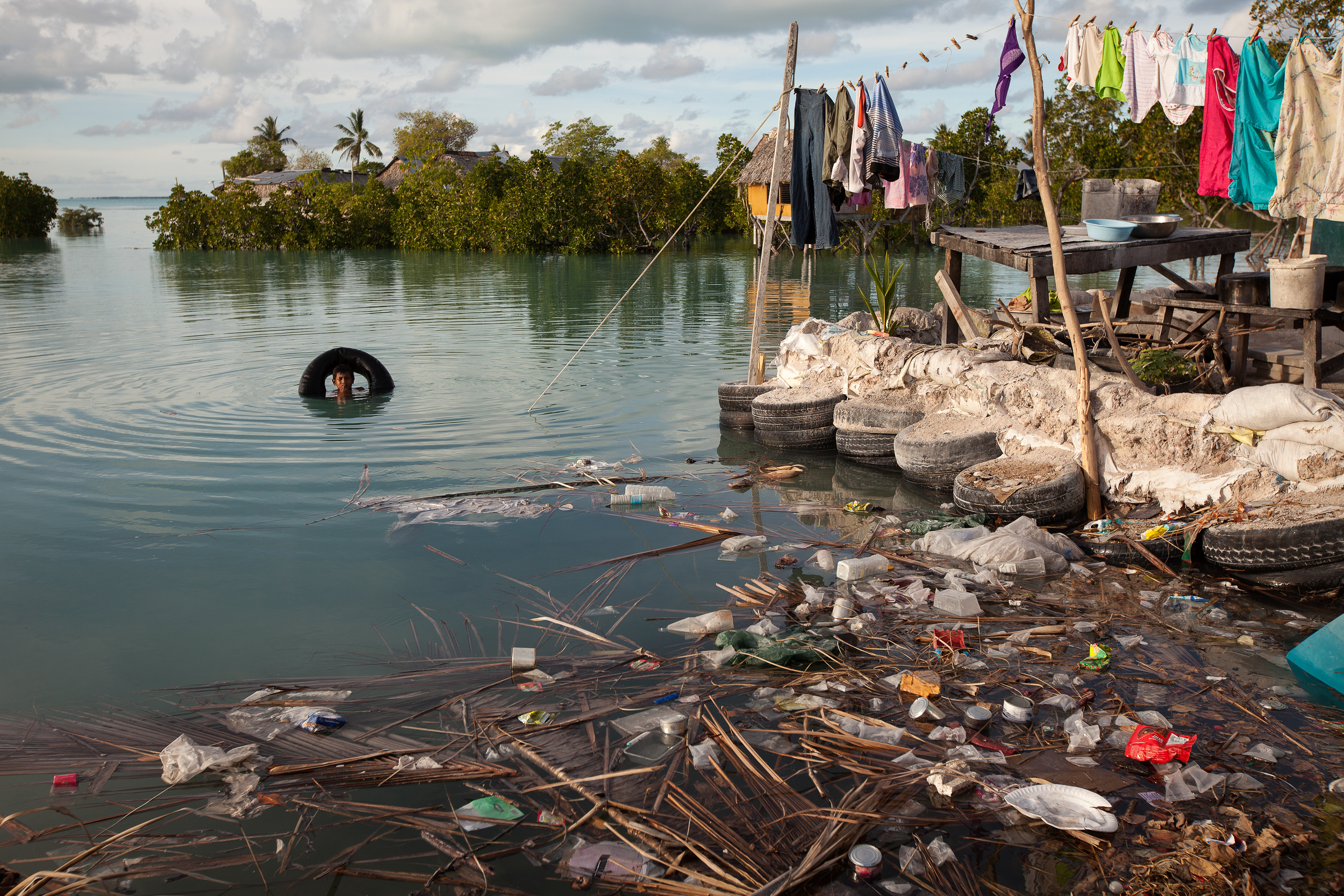 A boy swims in the lagoon next to his house in Temwaiku that is heavily polluted with rubbish brought in by the tide each day. Pollution is of course not caused by climate change, but the rising seas means less land and less money to deal with the basics.
