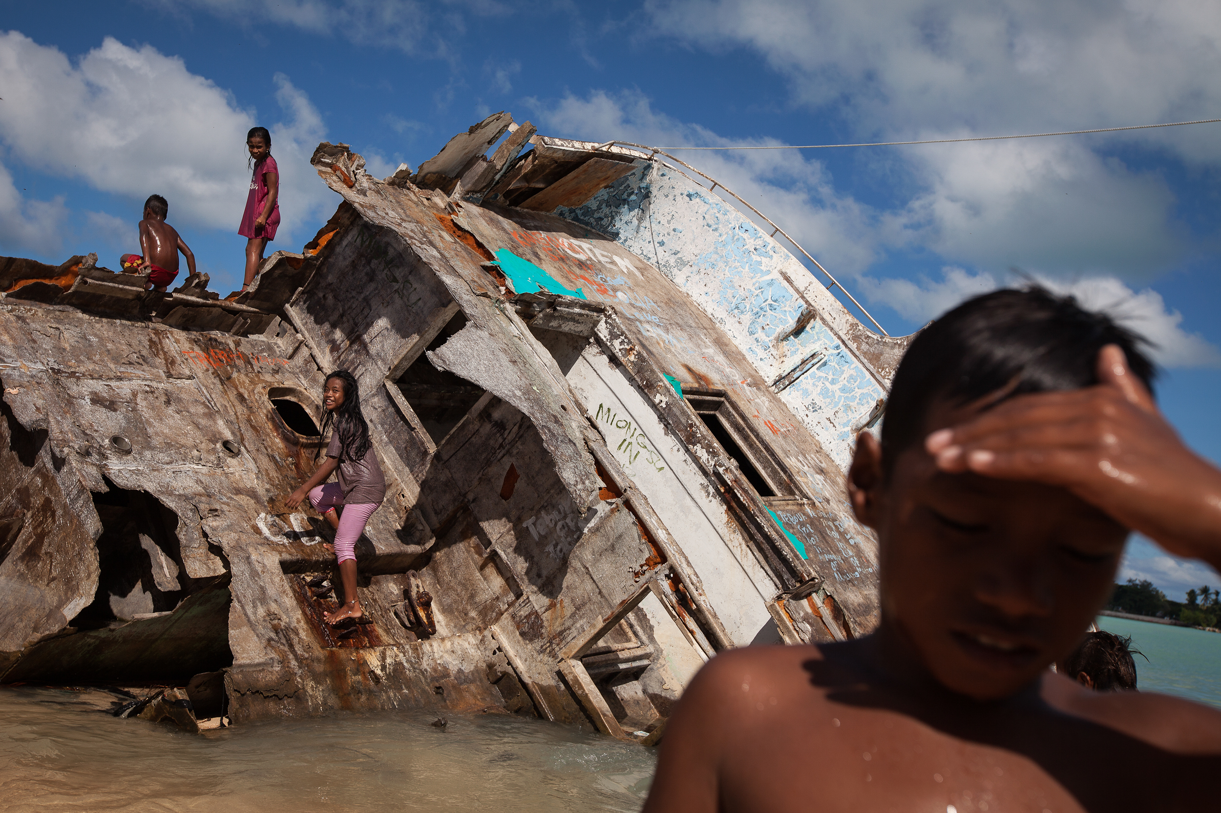 A boat washed ashore on Red Beach during a storm in 2013 now serves as play equipment for the local Betio kids. Betio is the most crowded and densely populated slum area in South Tarawa, with serious pollution and fresh water problems.