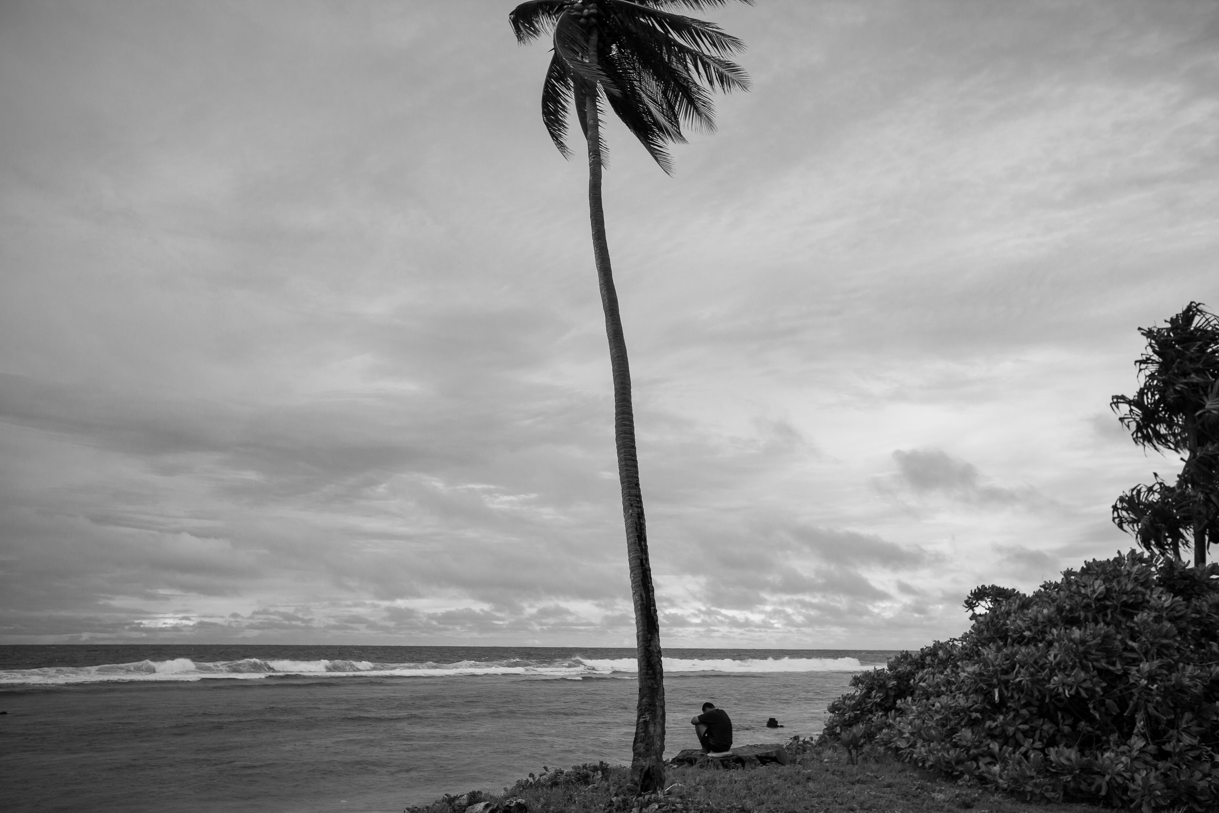An Iranian refugee looks out to sea outside Ijuw camp. Refugees on Nauru feel an acute sense of being stuck in limbo. Those accepted as refugees were released into the community on a 6 month visa, which have long expired and despite frequent queries to immigration, have not been told what will come next. Others whose claims are still being processed continue to be held in detention almost two years after arriving on Nauru.