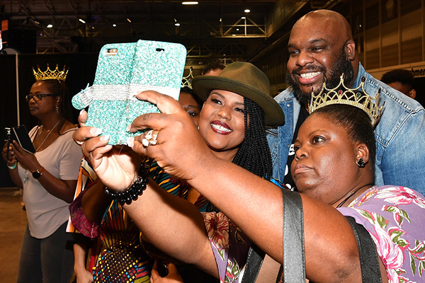 John and Aventer Gray stop to pose for a photo with a fan at Essence Fest (Credit: Paras Griffin/Getty )