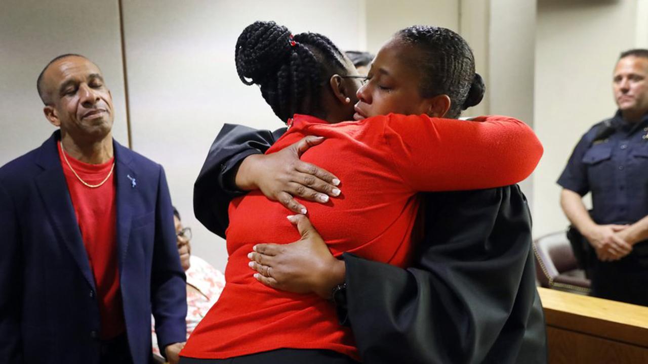 Judge Tammy Kemp gives Botham Jean's mother, Allison Jean, a hug while Botham's father, Bertrum Jean, looks on. (Tom Fox/The Dallas Morning News via AP, Pool)