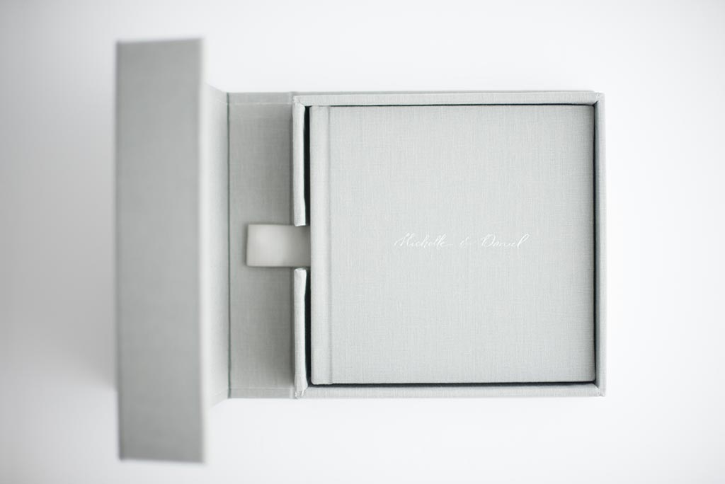 LINEN BOX - A perfect match to your linen album. A beautiful box out of the same linen used for your album covers. It features a unique, joint panel construction that unfolds to reveal your album inside and has a matching ribbon tab to lift your album for easy access. Price $275