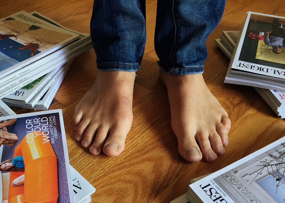 Bare feet surrounded by magazines. Photo by Wokandpix.