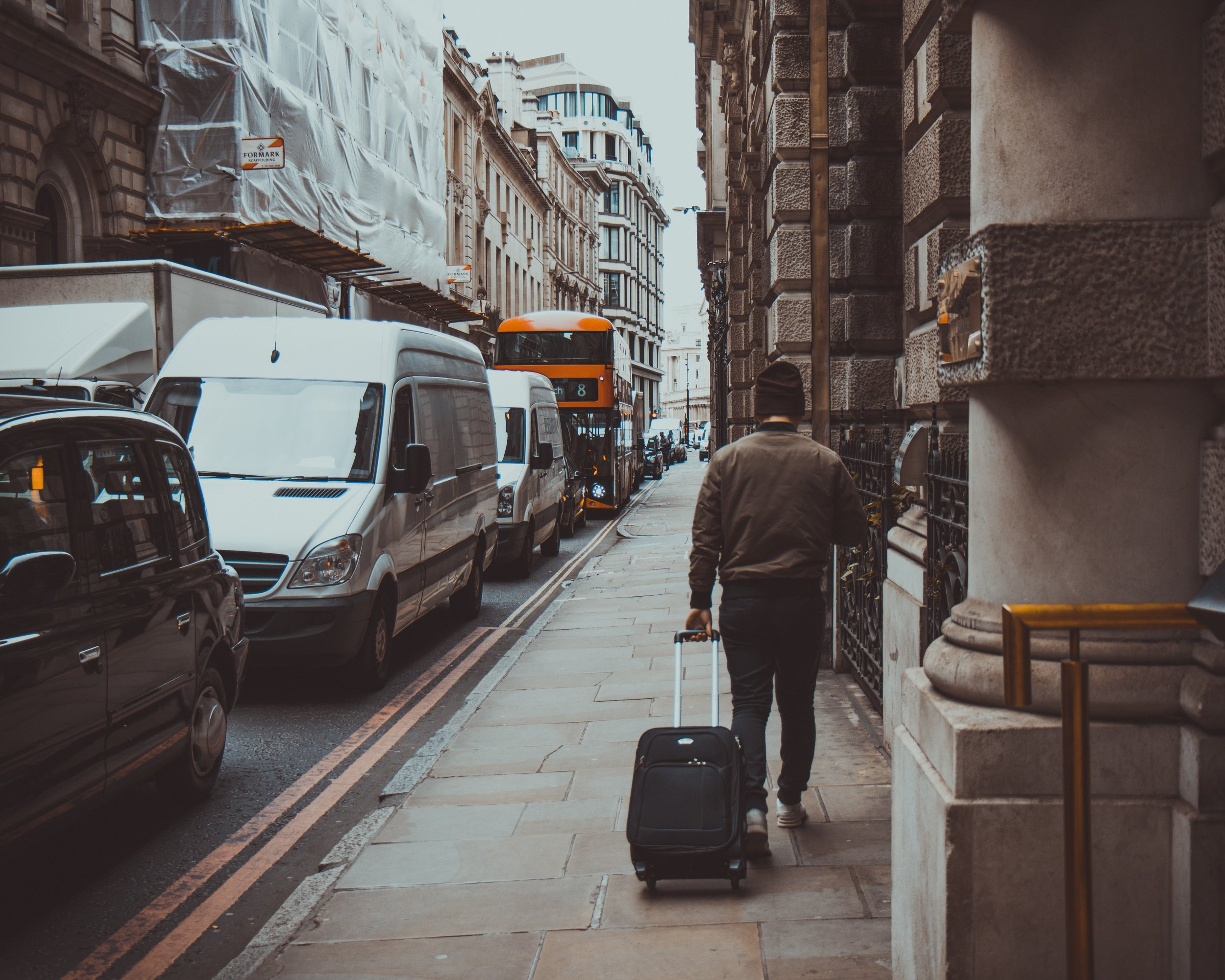 Man walking through the city with suitcase. Photo source Tomáš Gal on Pexels.