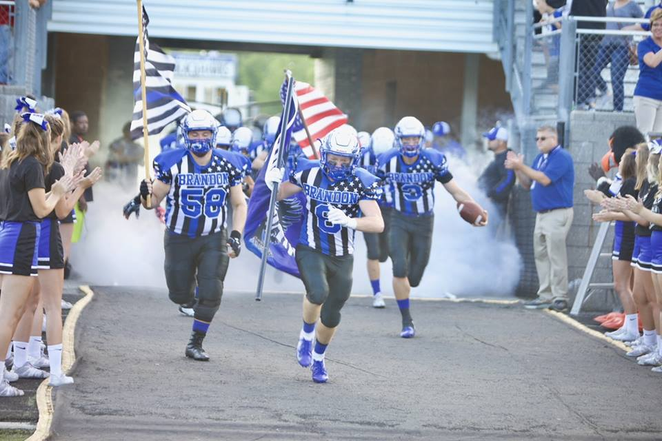 """Photo from the Brandon School District Facebook Page - Brandon in their Addix """"Never Quit"""" jerseys running onto the field."""