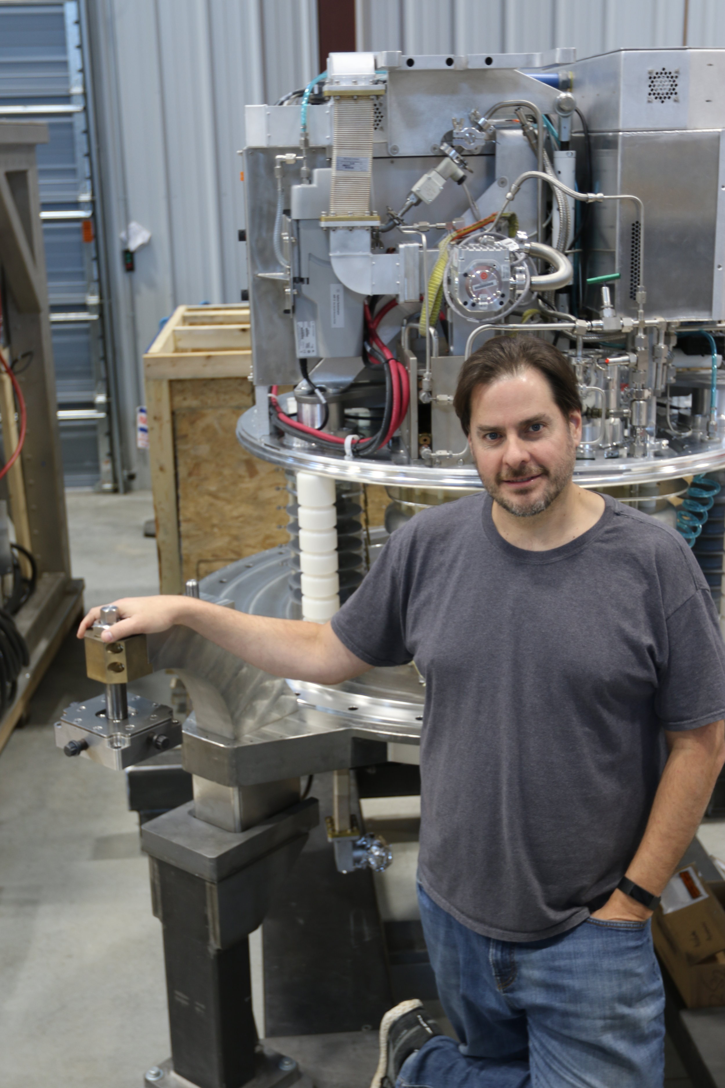 SHINE founder and CEO Greg Piefer poses in front of a Phoenix neutron generator being installed in SHINE's Janesville facility