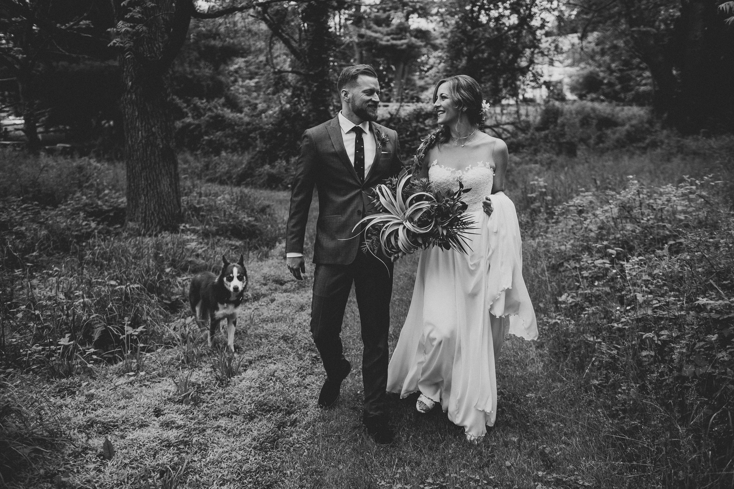 hudson-valley-farm-weddings-pioneer-farm-weddings-warwick-ny-newlyweds-walking-on-trail-with-dog.jpg