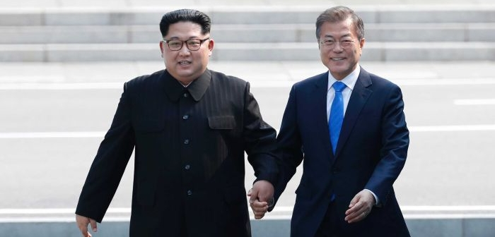 Kim Jong-un and Moon Jae-in hold hands as they cross the border into South Korean territory