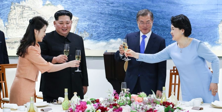 Ri Sol-ju and Kim Jung-sook lean across their husbands to clink glasses at the state banquet
