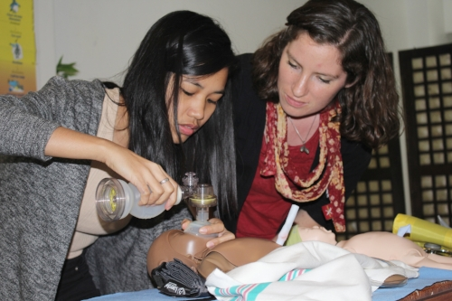 """Diploma Scholar Hannah teaching Helping Babies Survive classes for local midwives in the Philippines. This interactive simulator called NeoNatalie can be donated to allow local midwives to continue training in a """"Low Dose, High Frequency"""" methodology long after the trainer has gone home, thereby improving maternal/child health and welfare for untold thousands in future years."""