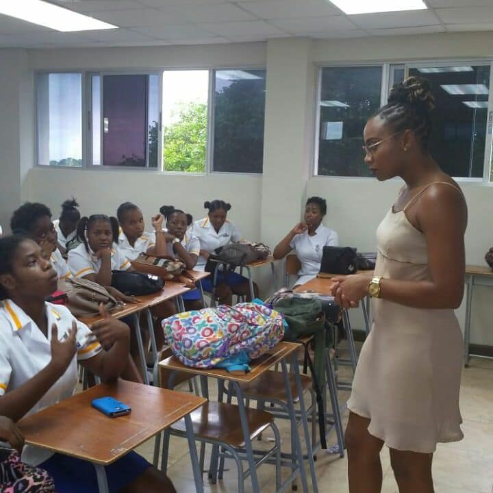 Krystal Tomlinson. engages a student of St. Hugh's Positive Society