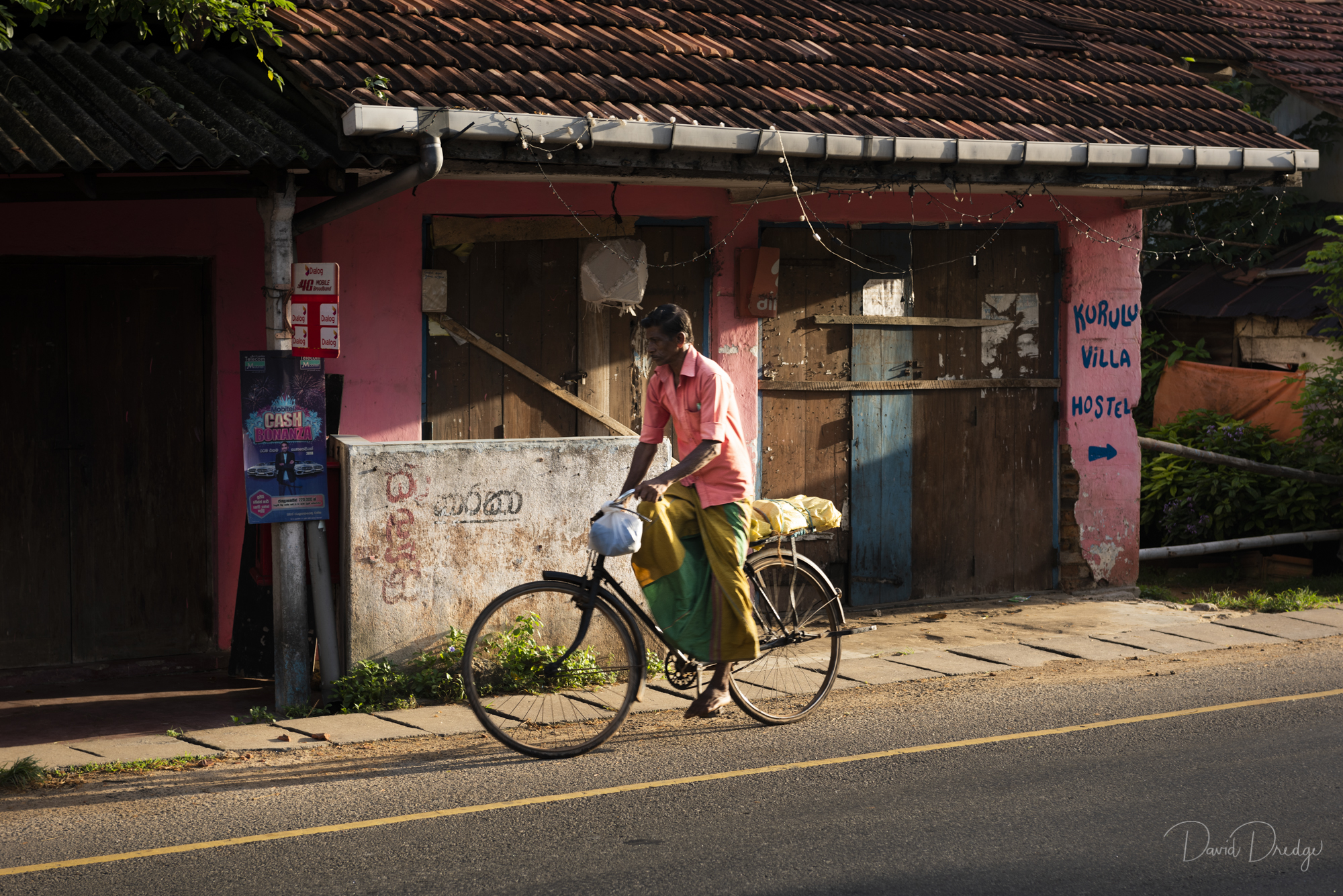 Early morning village scene man on a bicycle wearing and lungi