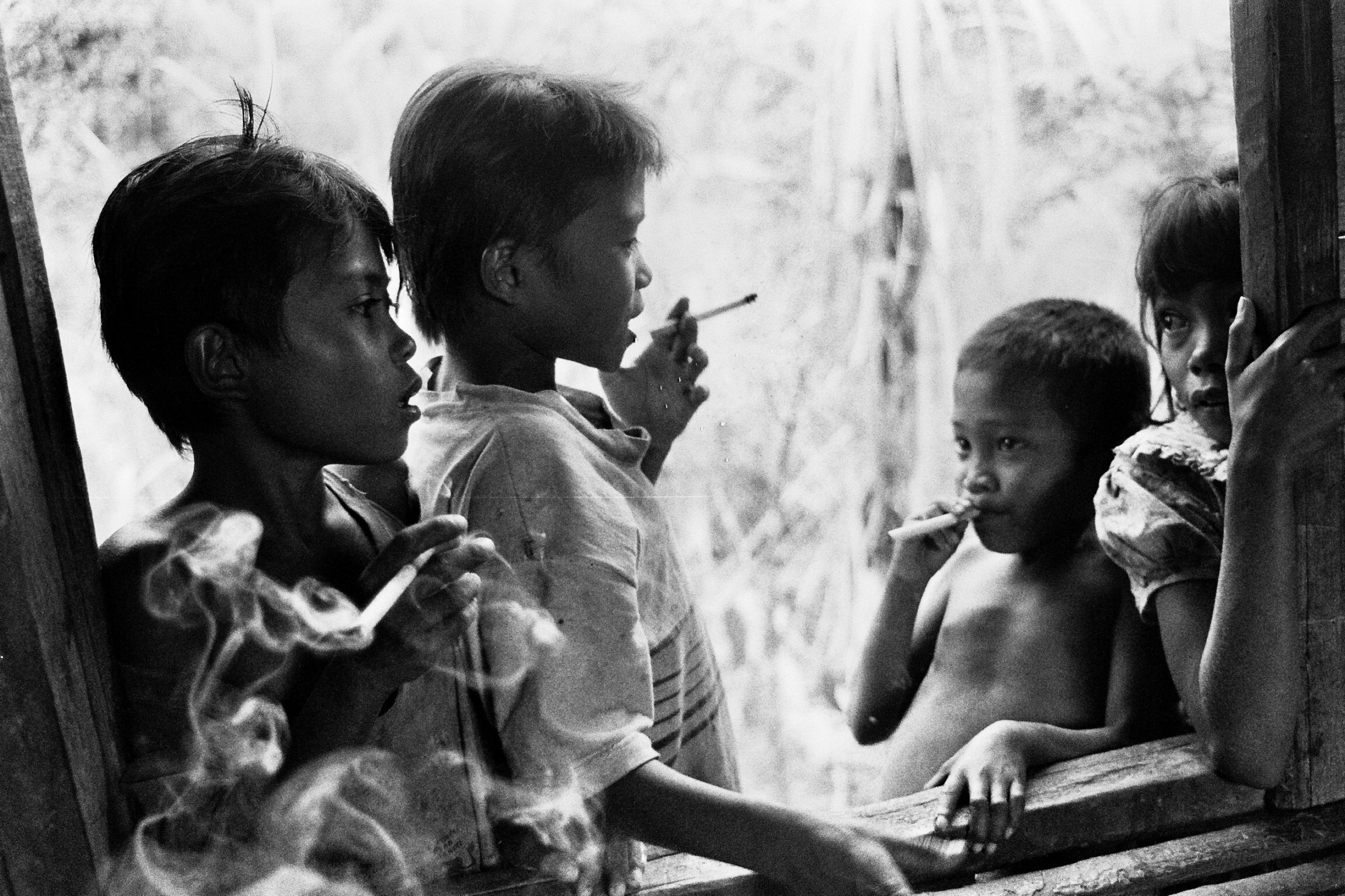 Cigarettes both clove and western had already been brought to the village and were valued by children and adults alike. The girl on the right wasn't part of the boy gang.