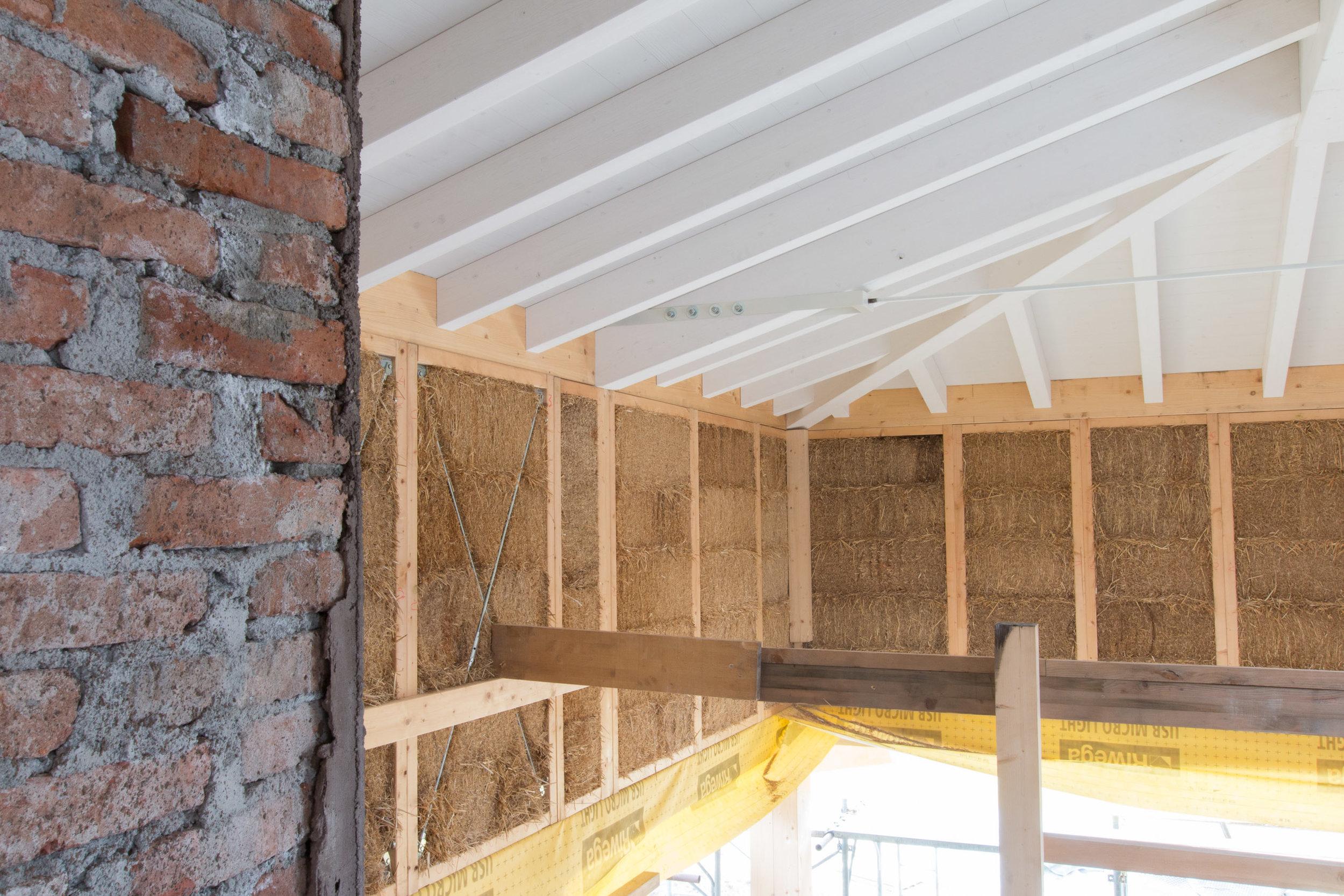 Il tetto in paglia posato sui muri prefabbricati in legno e paglia
