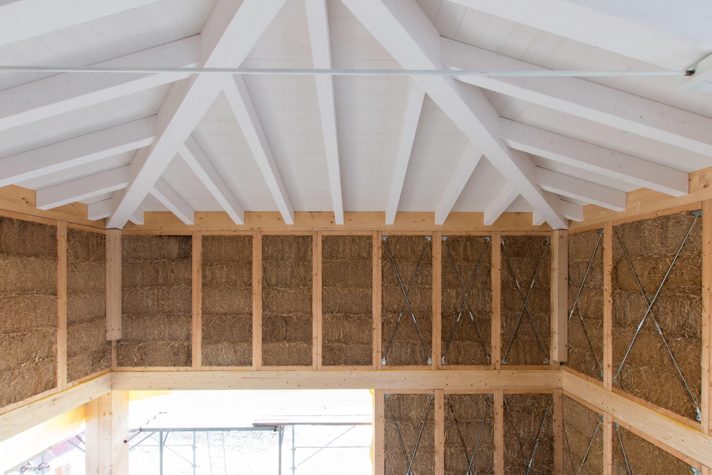 Il tetto in paglia posa su un cordolo in legno di partenza, appoggiato sui muri prefabbricati in paglia e legno