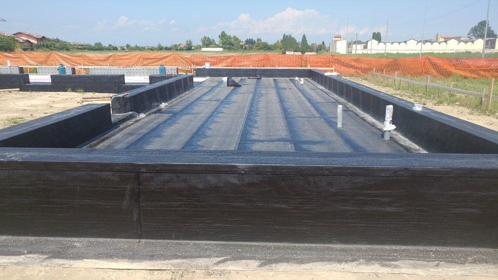 Impermeabilizzazione della platea in cemento armato, prima della posa della casa in legno e paglia