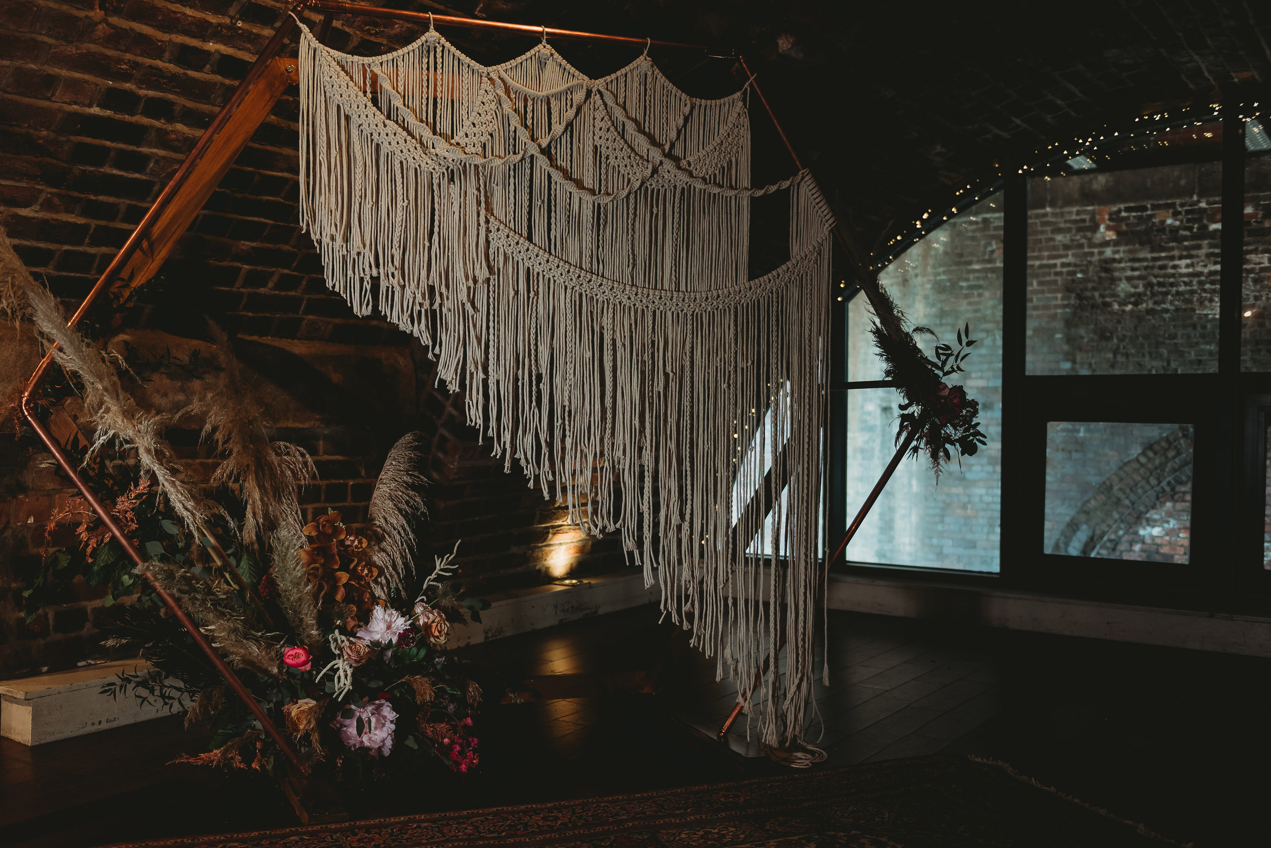 Handmade macrame wedding decor in an industrial wedding venue. See the full shoot here.