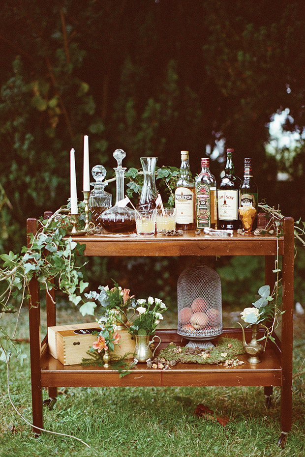 Relaxed help yourself wedding bar cart with foraged greenery and boho styling featured on  One Fab Day .