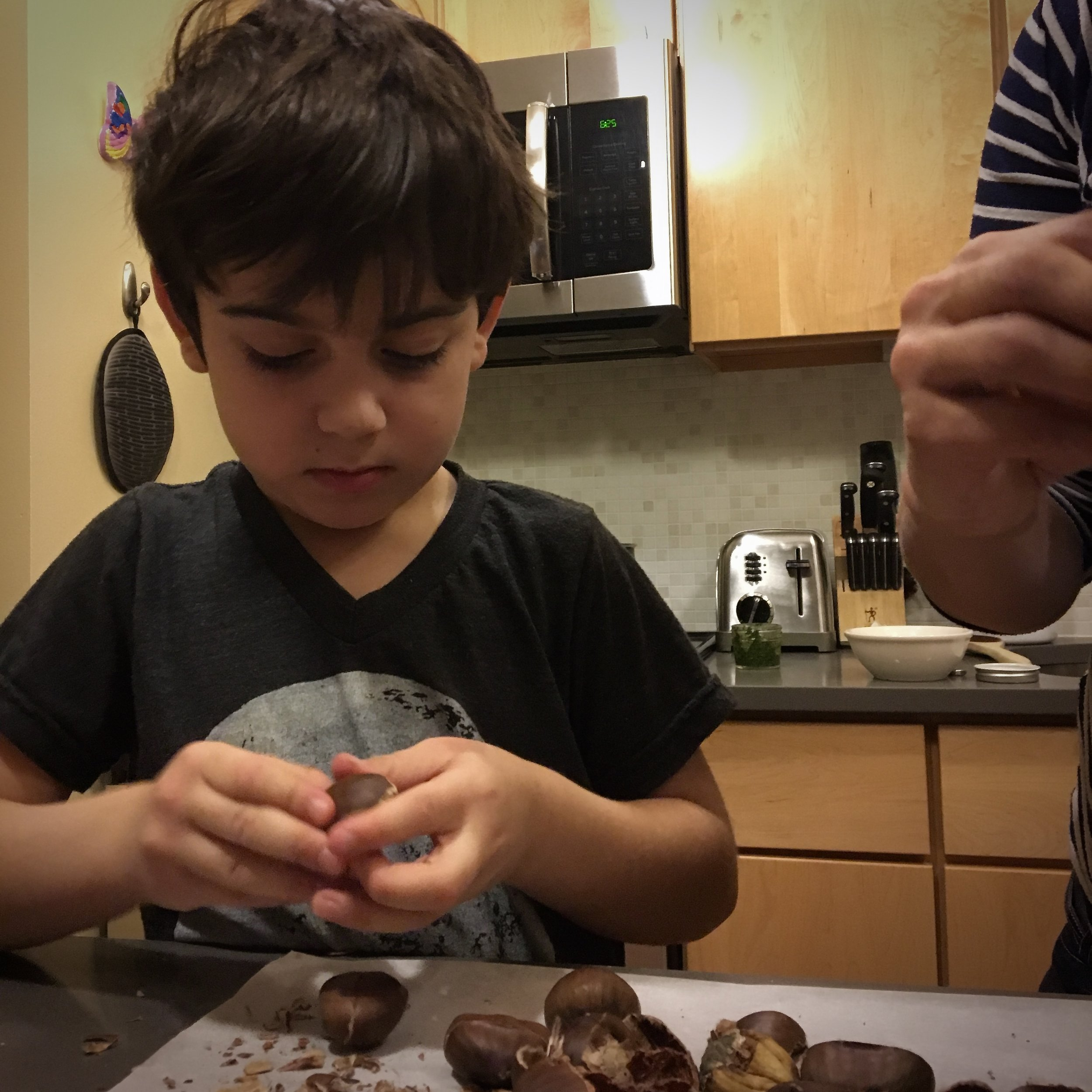 Shell nuts - Give them a pile of pistachios, chestnuts, edamame, peas, or anything else requiring separation from the shell -- even a pomegranate if you cover your child (and your kitchen) in a red apron first. Their focus and little fingers will be amused by this task for hours.