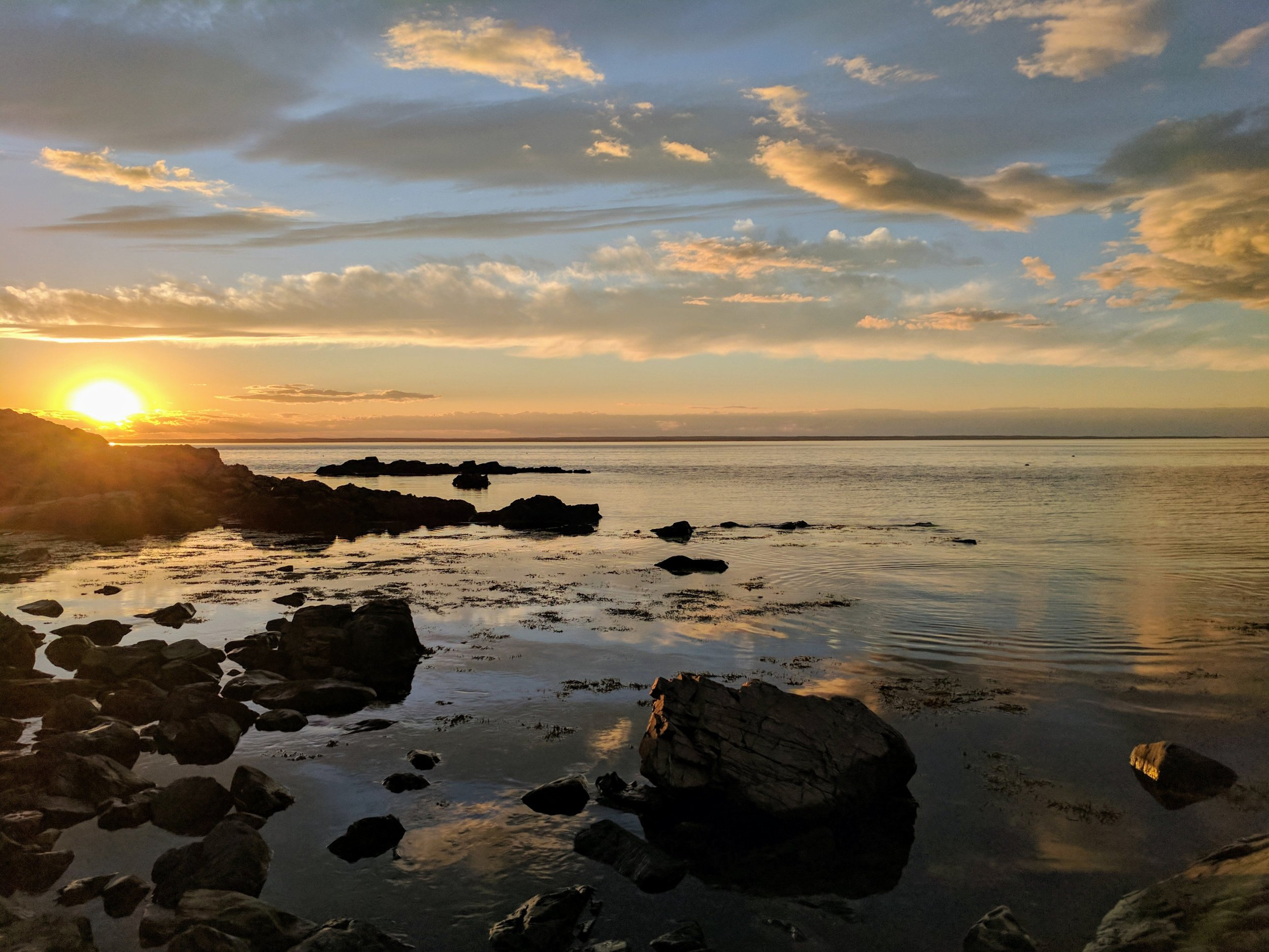 sunset-over-water-by-rocky-shore_4460x4460.jpg