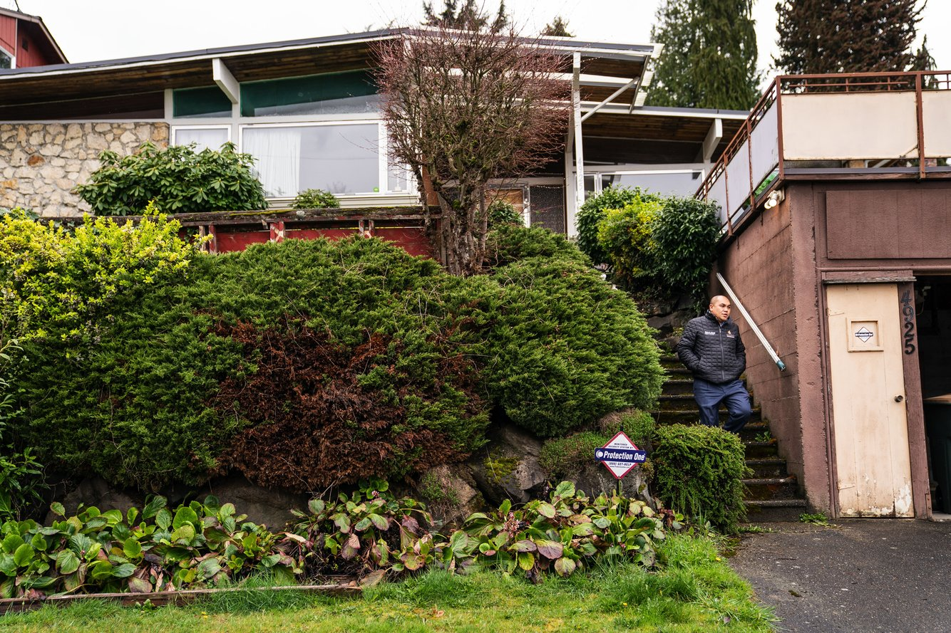 """Mustapha """"Moose"""" Math, a broker with John L. Scott, shows a property at 4925 29th Ave. S. in South Seattle. The midcentury house is an estate sale and will be sold as-is, and likely list somewhere around $800,000. (Dean Rutz/The Seattle Times)"""