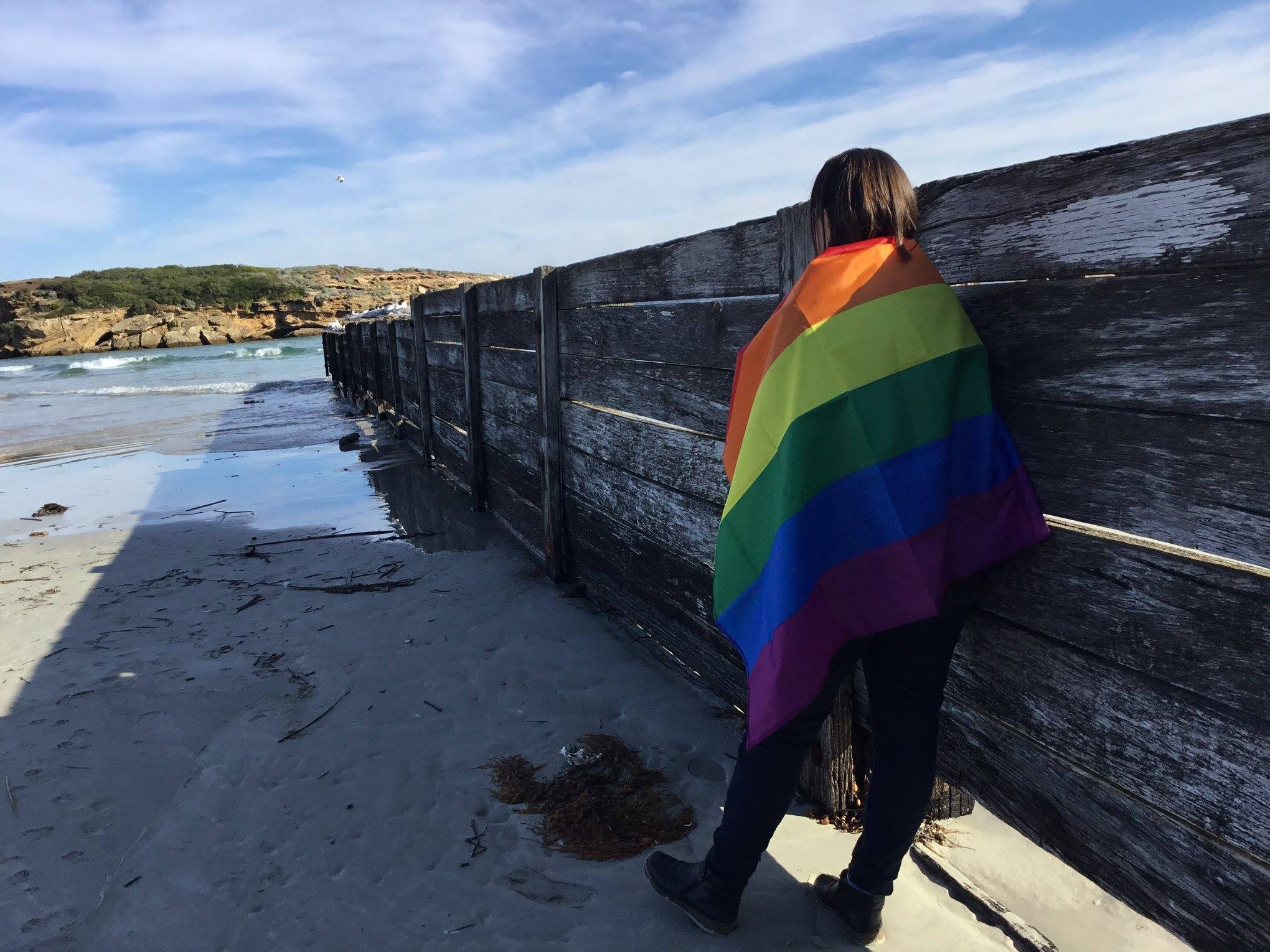A person draped in a pride rainbow flag stands on a beach and looks out into the distance.