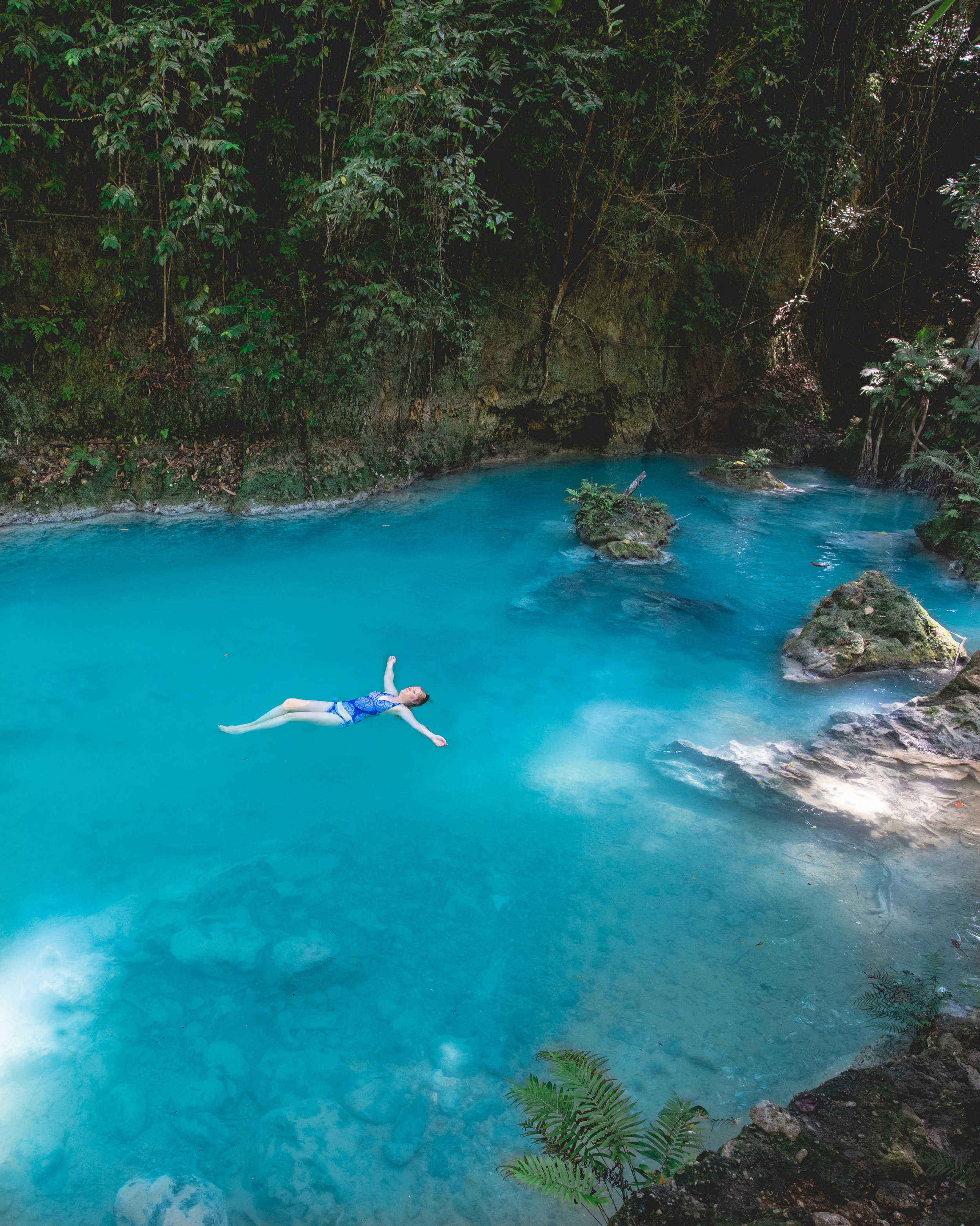 Floating in the river by Kawasan Falls
