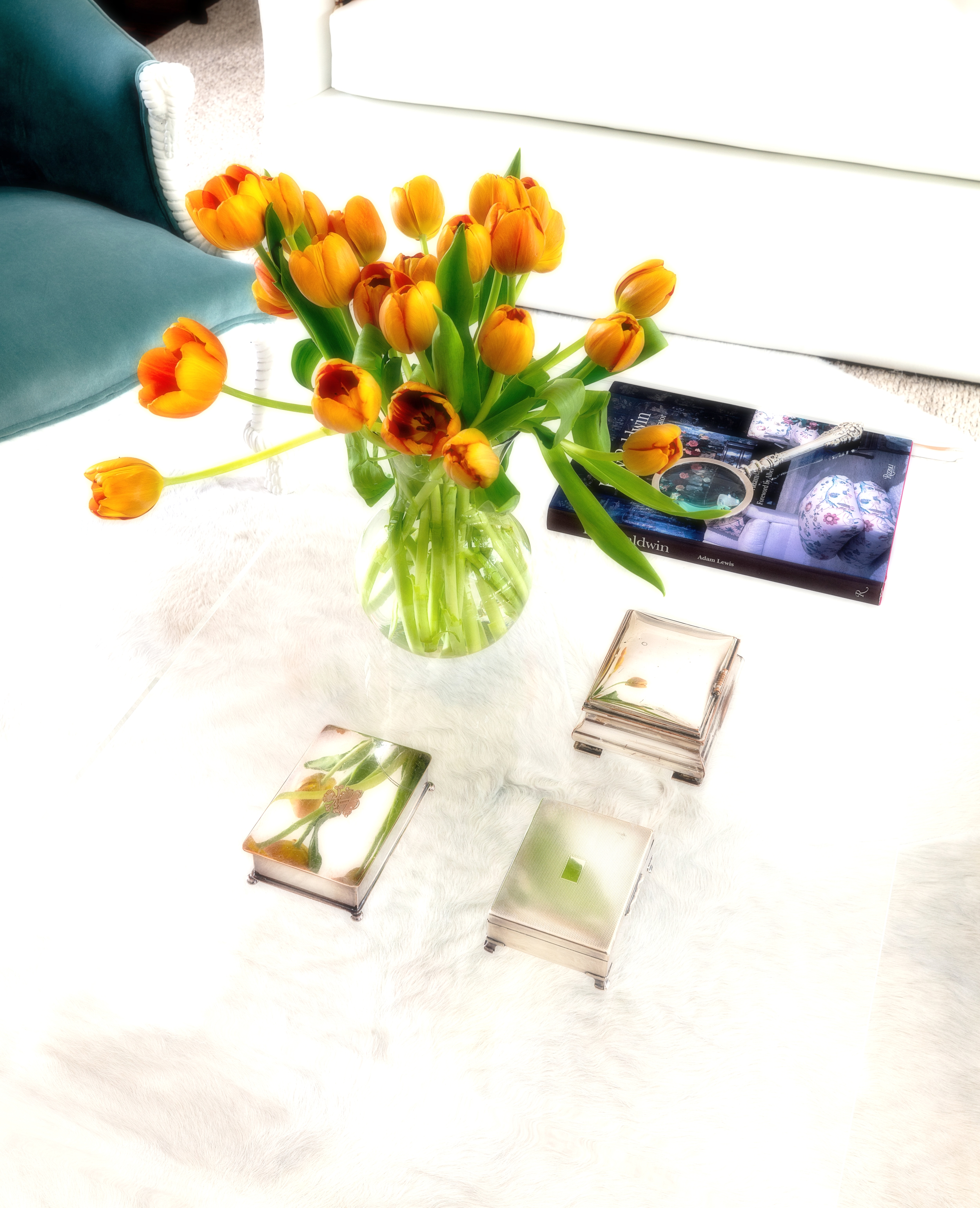 An acrylic cocktail table, vintage sterling boxes from my personal collection, Billy   Baldwin...an inspiration and icon, and orange tulips.  What more could you need?
