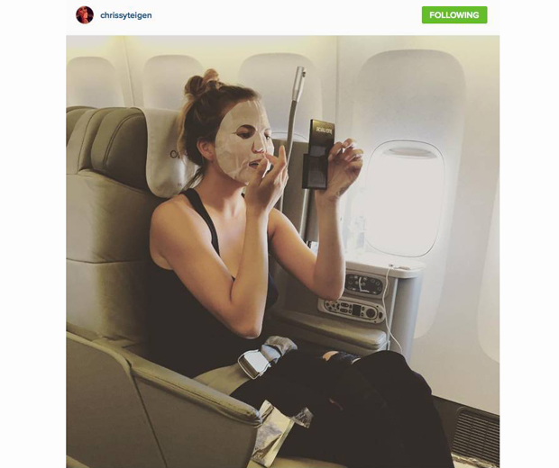 Chrissy Teigen travelling in style with her tissue sheet mask.