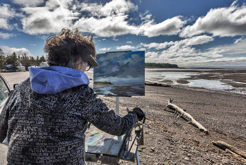 Nancy Tankersley works during 2018's Parrsboro Plein Air Festival. Her work, Lifting Clouds, featuring Parrsboro harbour was the winner of the competition. This year's festival is set for June 20 to 23 with 30 painters from across North America coming to the Parrsboro area. - Contributed - Amherst News