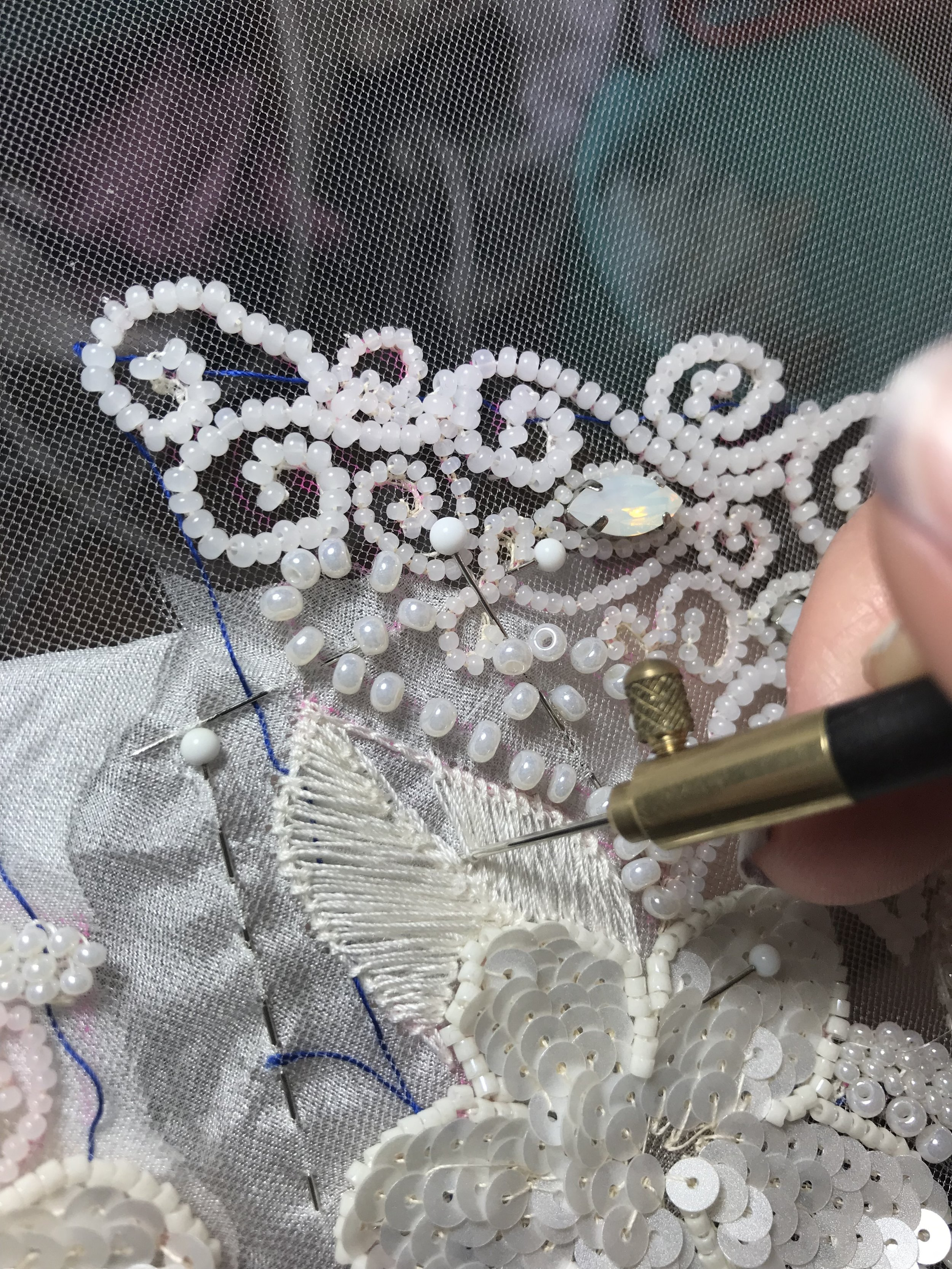 embroidering the last piece of the wedding dress