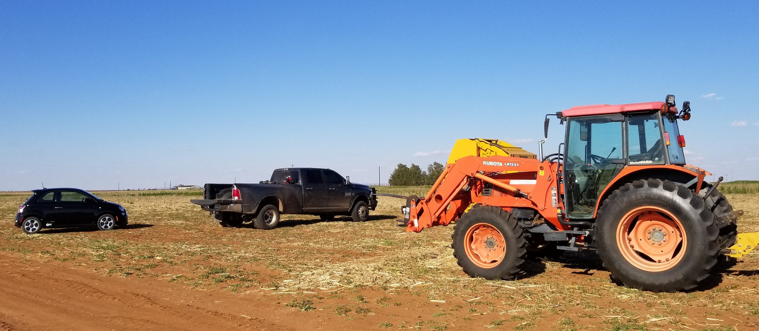 Our little fiat next to my brother's truck and loader