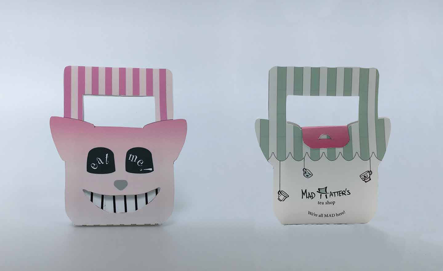 """scone packaging featuring a die cut smile cheshire cat in the front and a branded mad hatter's """"mad hatter"""" with top hat in back"""