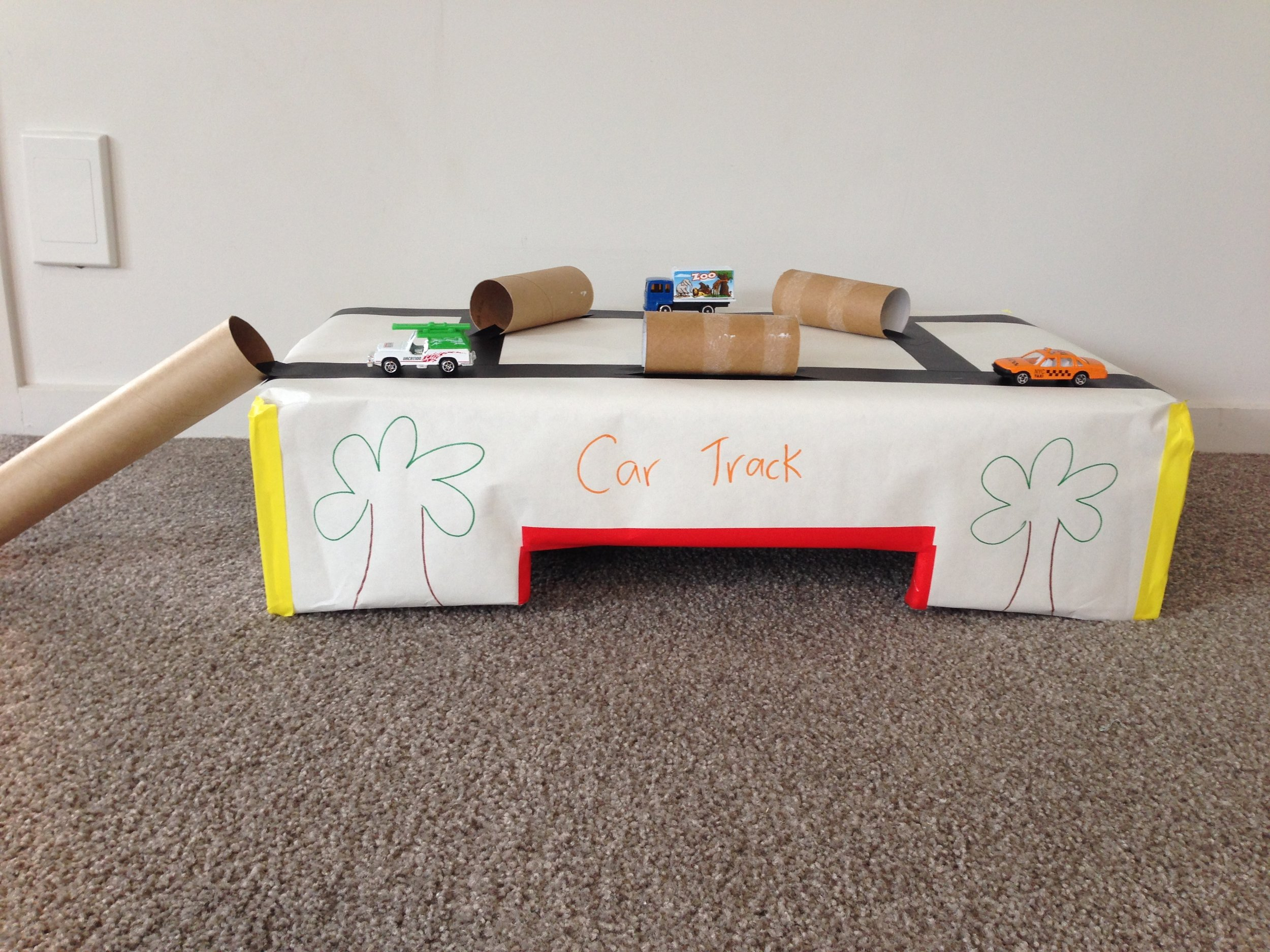 Car Track - Instructions1. Cover a cardboard box in craft paper, or leave it plain if it hasn't got any labelling on it2. Tape off pieces of road using black tape3. Cellotape or glue toilet paper rolls on the roads for tunnels4. Cellotape or glue a handi towel roll onto one end as a long tunnel or ramp5. Cut tunnels in the bottom of the box for the cars to go under aswell