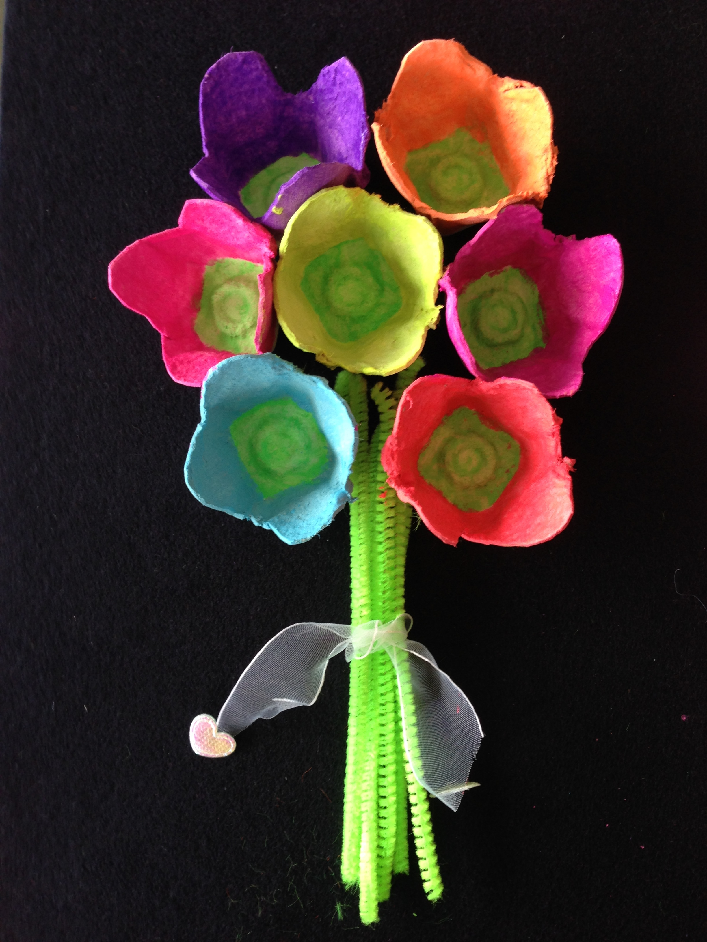 Egg carton flowers - Instructions1. Cut out the sections that the eggs sit in from the egg carton2. Paint these as flowers in any colors you like3. Glue them to a piece of wood or board4. Gather a few green pipe cleaners together and tie a ribbon around them5. Glue pipe cleaners to the wood as the stems of the flowers