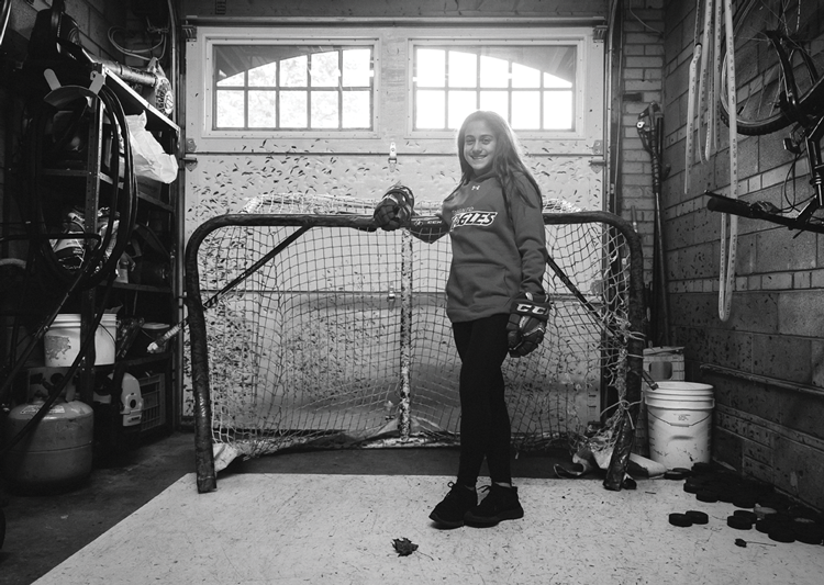 Emma Venusio standing in front of a hockey net