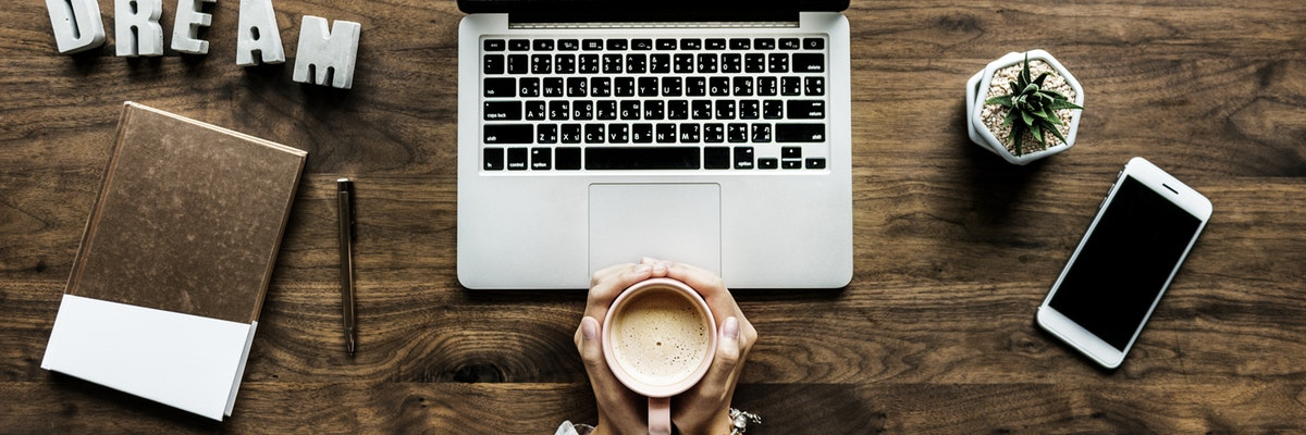 Computer on desk with person holding coffee mug